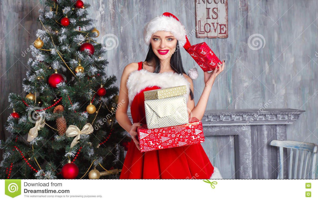 f9a100930604 Beautiful girl wearing santa claus clothes . Smiling woman with big and  small gift. Women on dress and santa`s hat. Santa`s helper