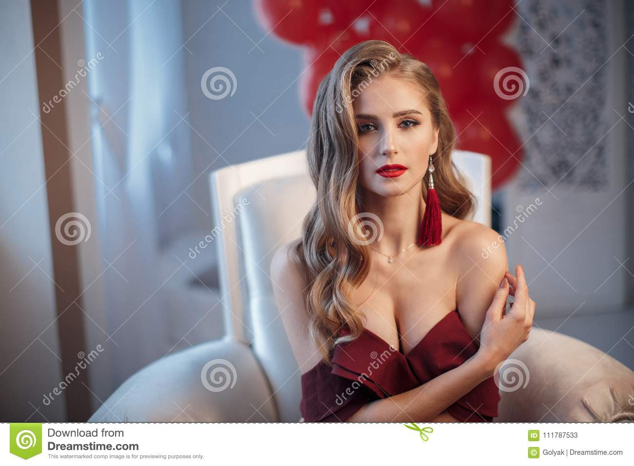 Beautiful woman in an elegant outdoor dress posing alone, sitting in a chair