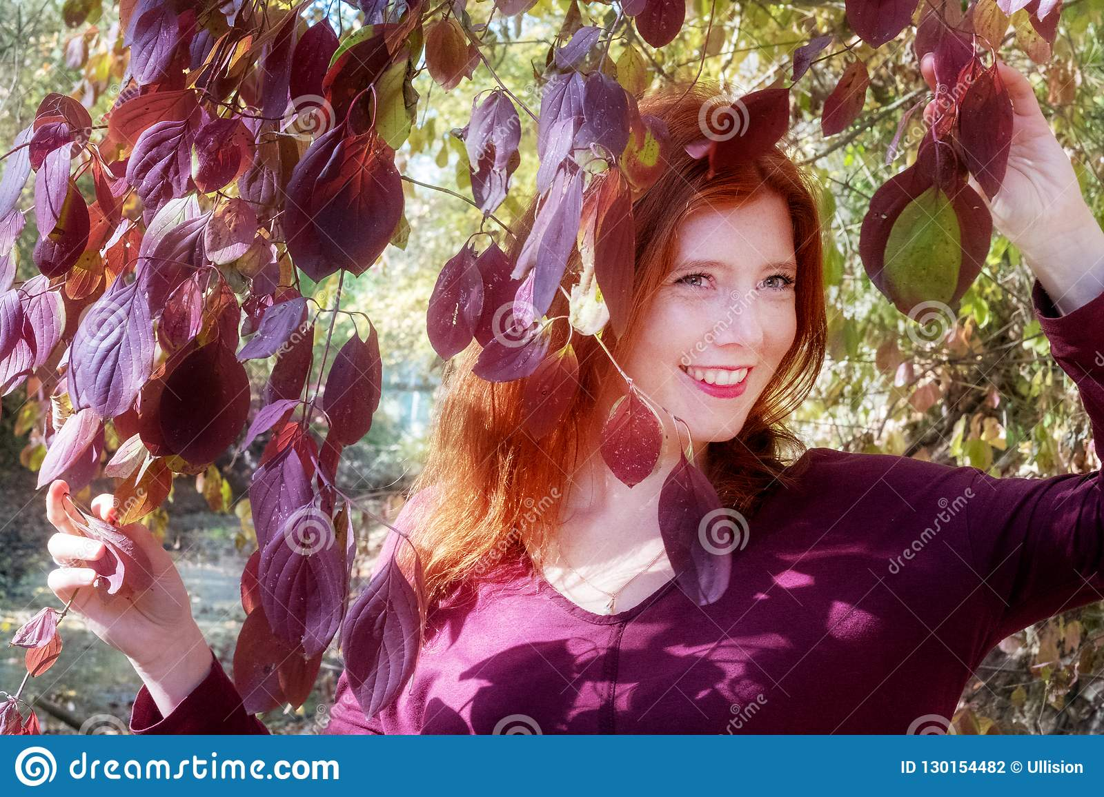 Beautiful lovely young foxy fiery red-haired girl, among violet lilac autumn bush, holding the leaves in both hands