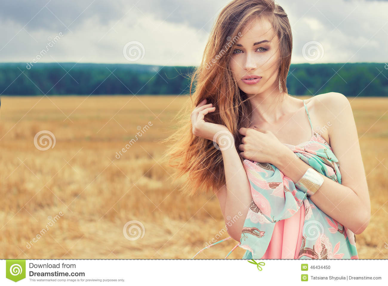 Beautiful romantic girl with red hair wearing a colored dress, the wind standing in the field on a cloudy summer day