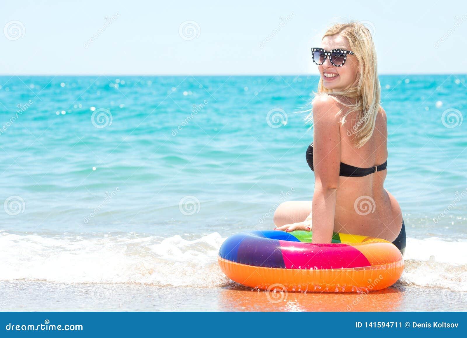 Beautiful woman in bikini with inflatable circle sitting on the beach.