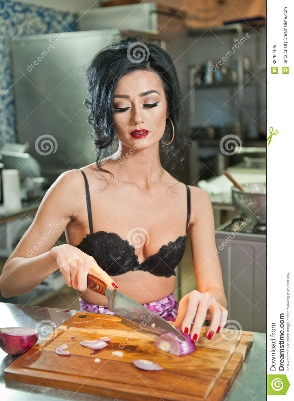 84317c4b29c60 Beautiful and woman in the kitchen. Smiling brunette preparing food. Young  girl wearing black bra cutting some onions on the wooden board.cute sensual  young ...