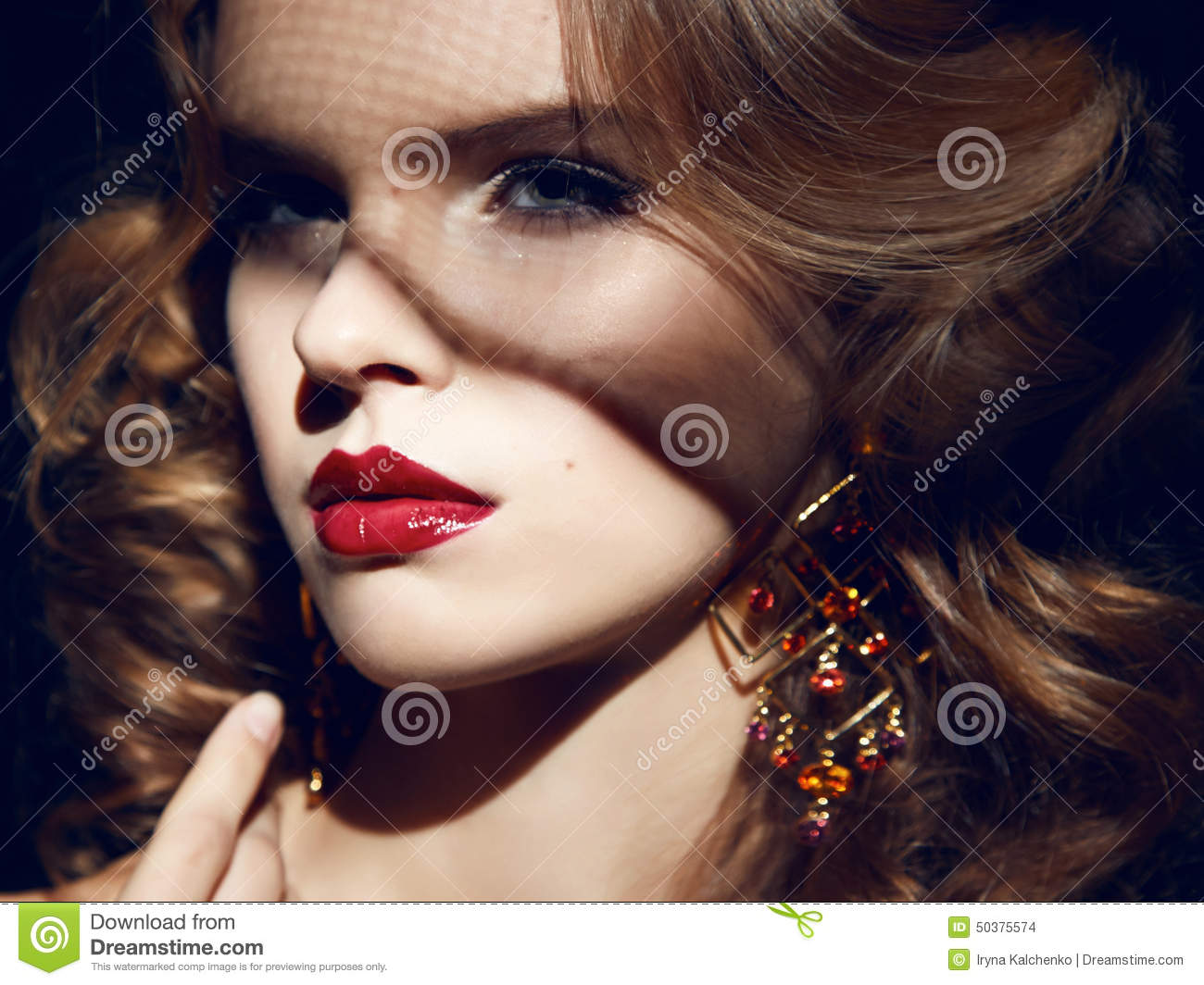 Closeup of the face belong to beautiful young blonde girl with curly hair pure snow white skin and bright makeup red lips, red lipstick, long earrings in ...