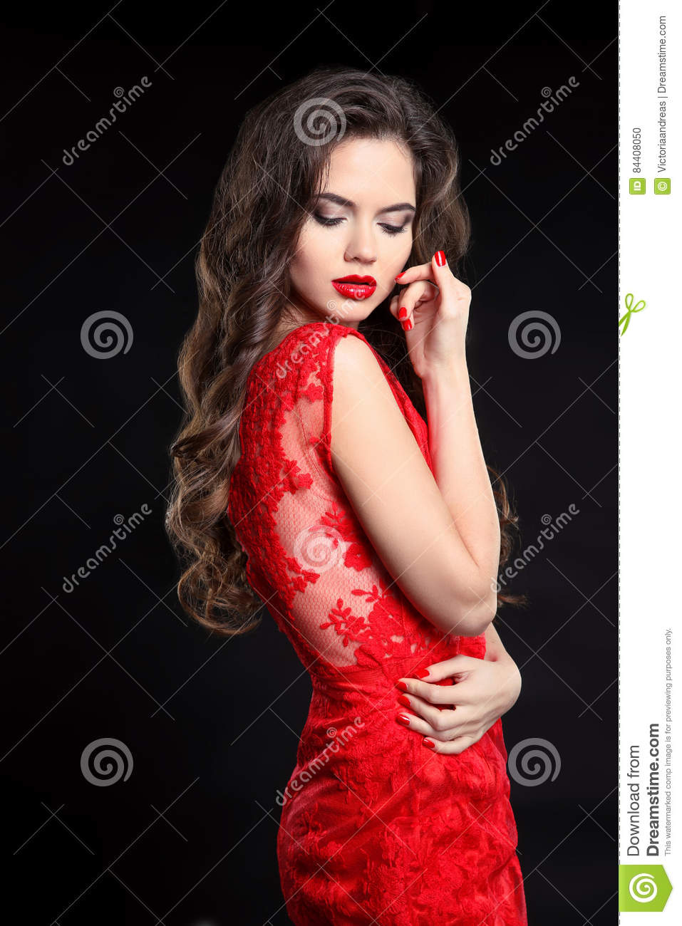 605303920e637 Beautiful woman posing in red dress isolated on black background. Beauty  makeup. Long healthy curly hair. Fashion style studio photo. Manicured  nails.