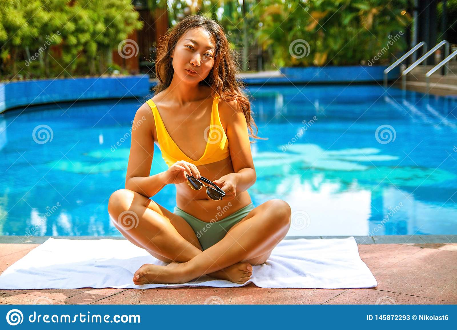 Beautiful asian woman relaxing in swimming pool in the hotel.