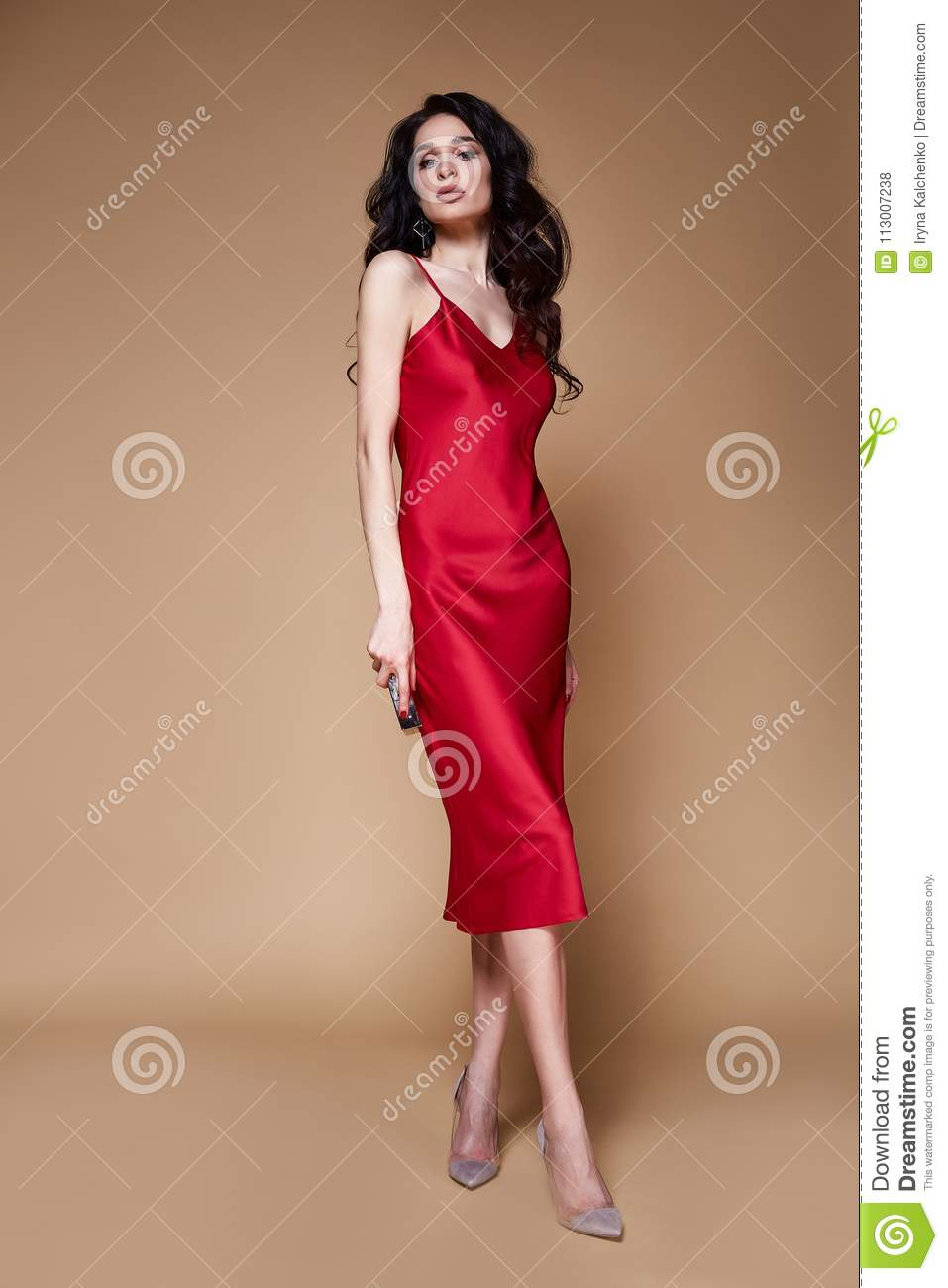 8748693b877 Beautiful young elegant woman brunette hair with evening makeup wearing  long red silk dress high heels shoes accessory bag fashion clothes for date  party ...