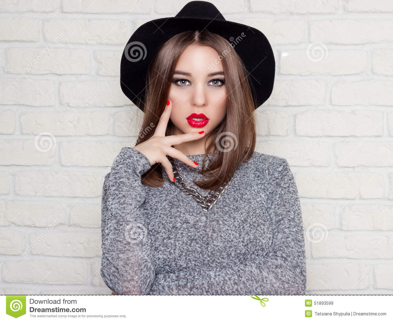 Beautiful young girl in a black hat with red full lips, bright makeup and painted my nails red