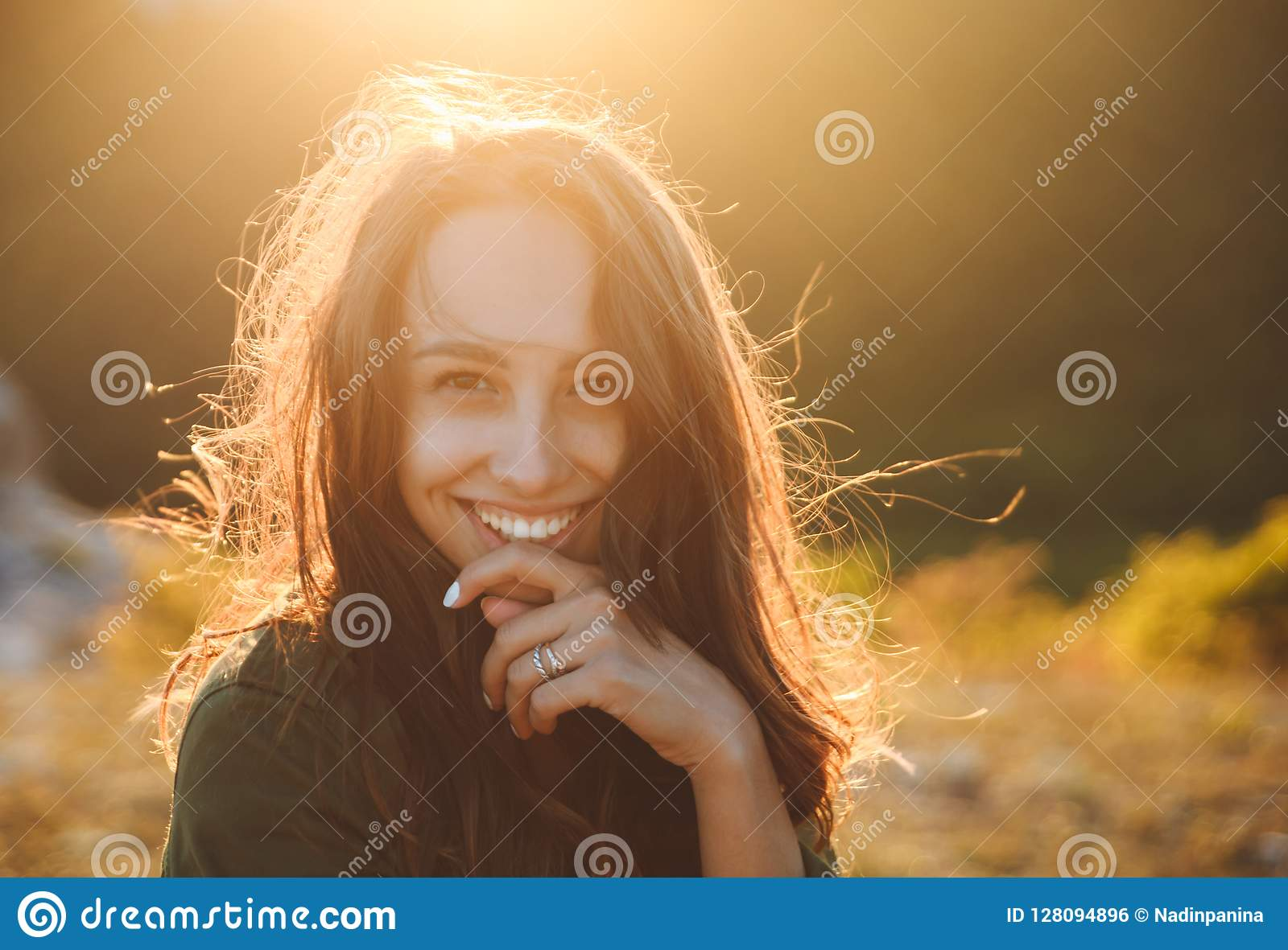 Beautiful young woman smiling on beautiful landscape in sunset time.