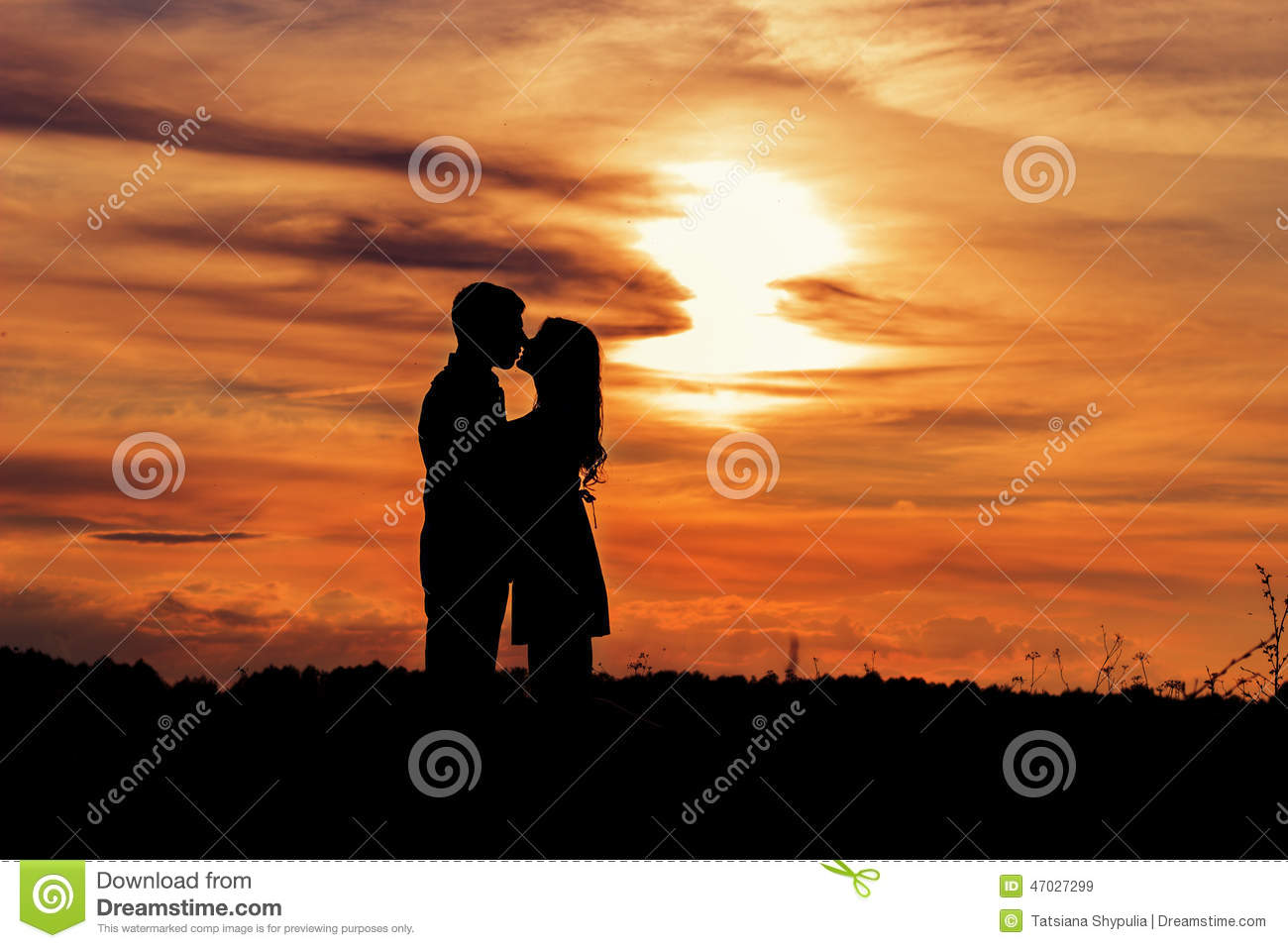 Beautiful shade loving happy couple kissing at sunset in a field of warm summer day