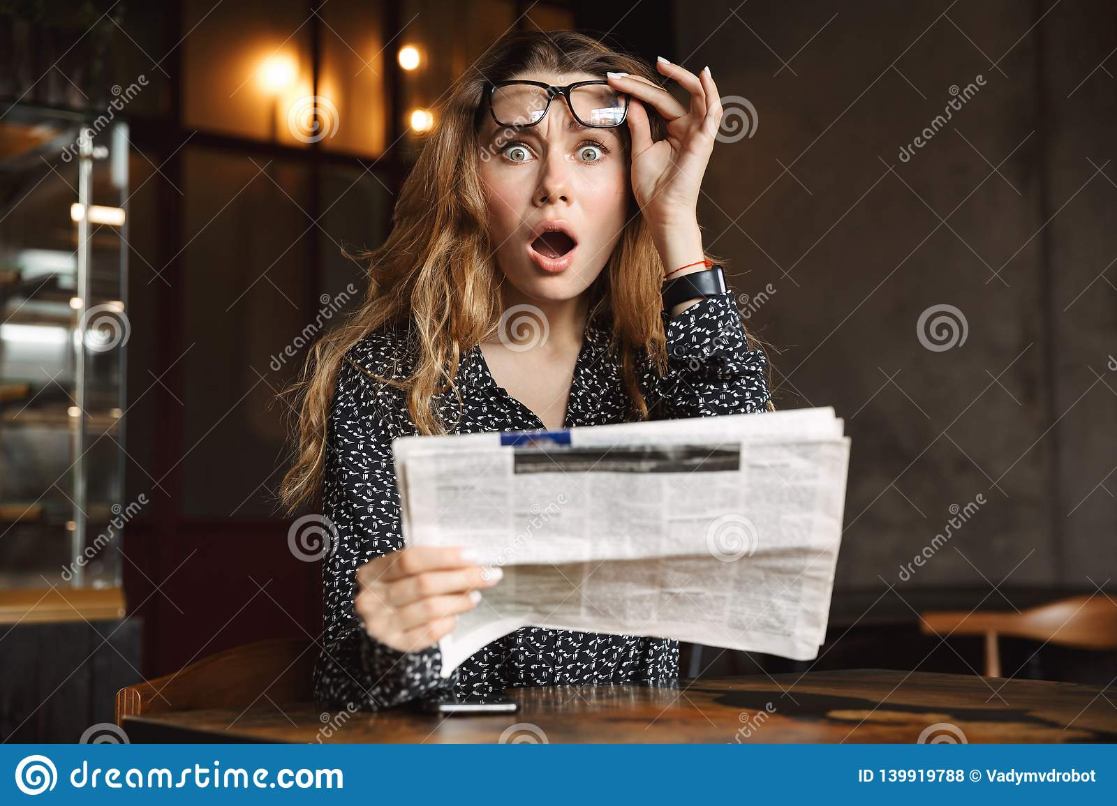 Beautiful shocked excited young woman sitting in cafe indoors reading newspaper