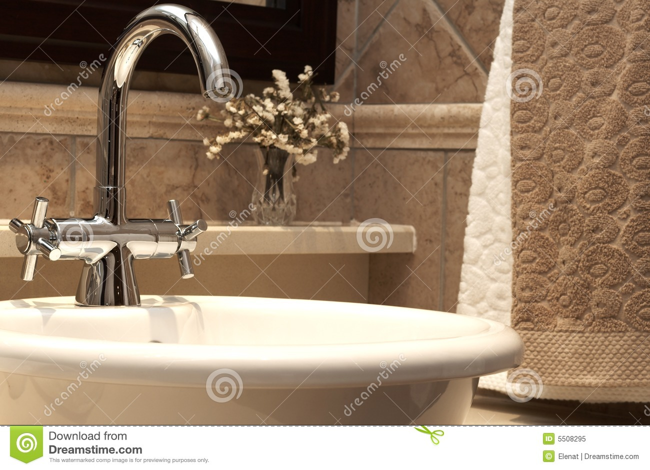 Beautiful sink in a bathroom with beige towels hanging next to it and ...