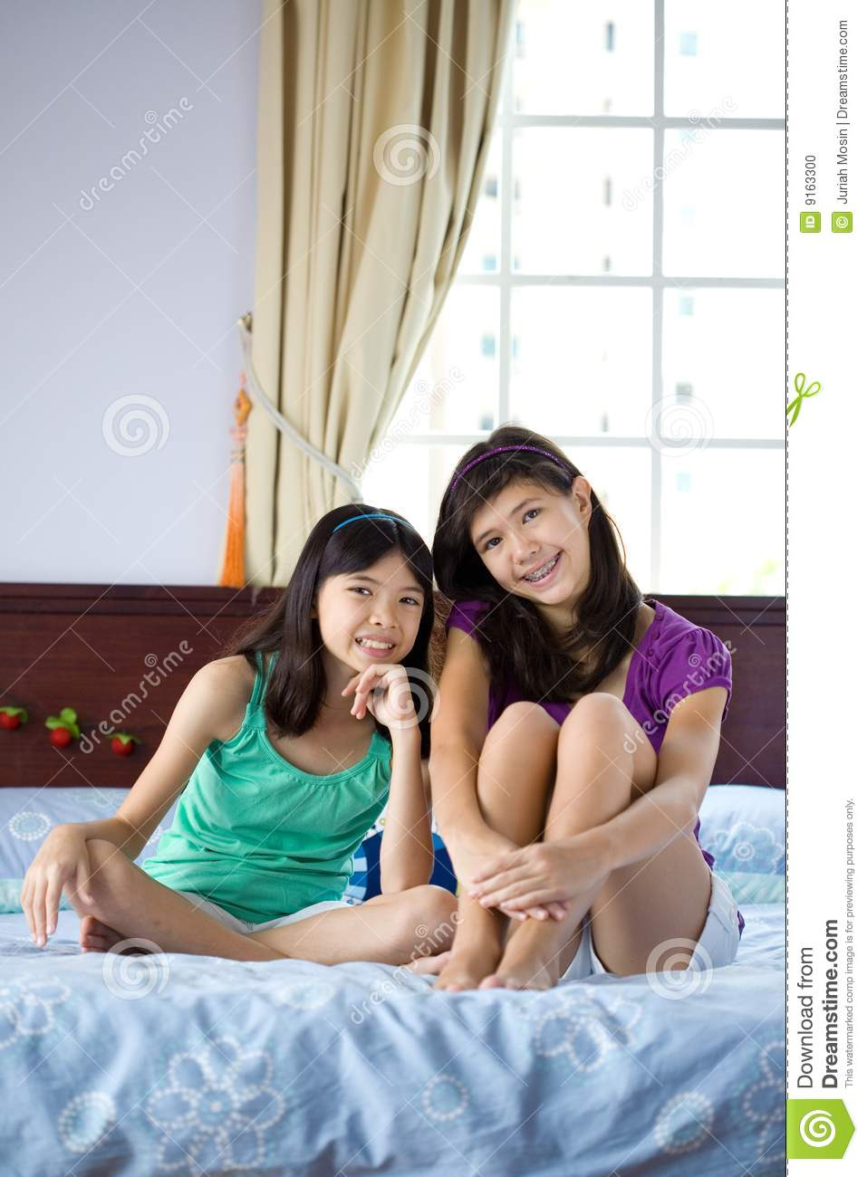 beautiful sisters relaxing at home stock photo image. Black Bedroom Furniture Sets. Home Design Ideas