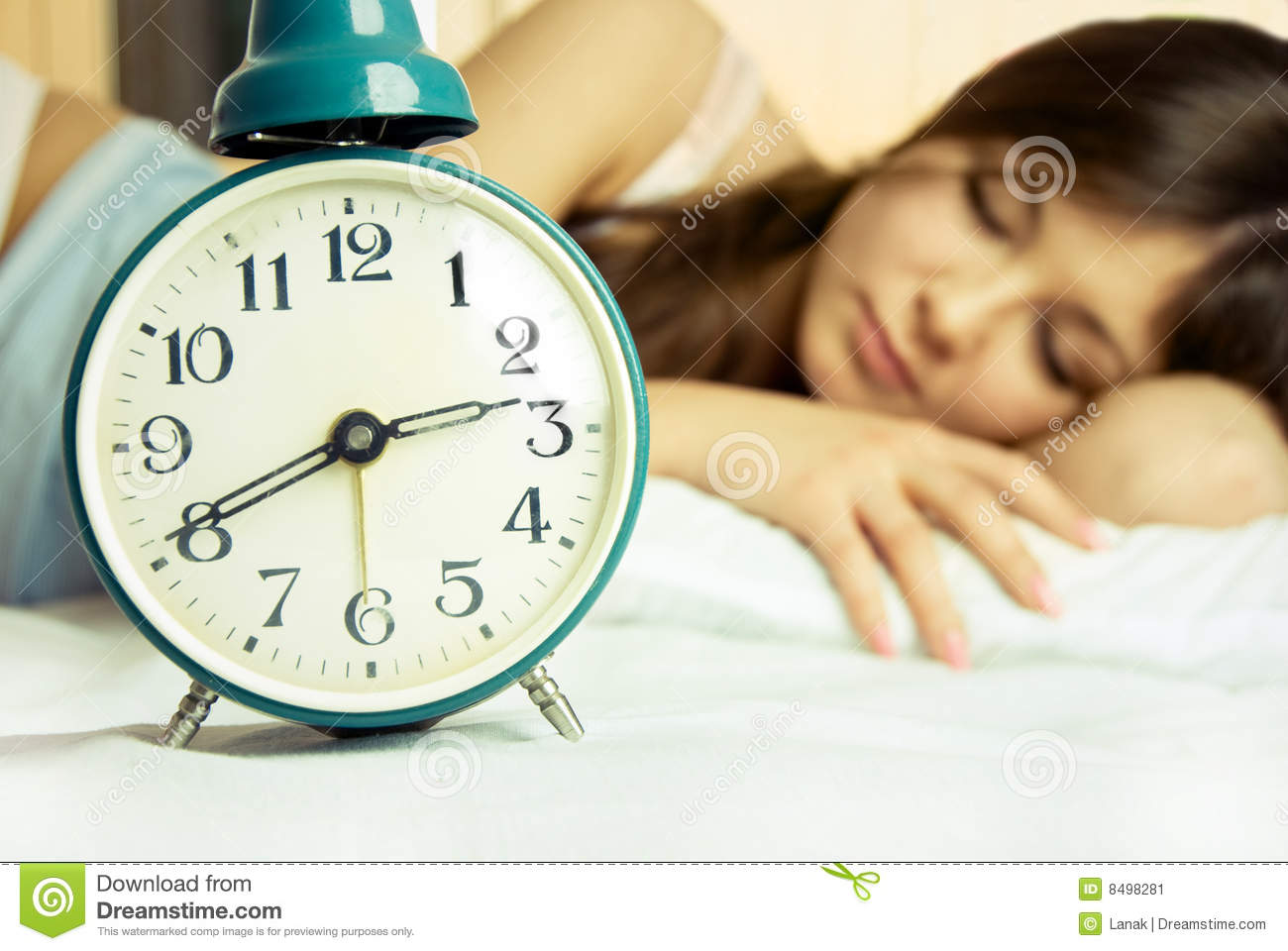 Beautiful sleeping woman with an alarm clock