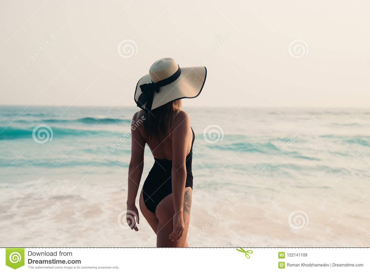7a78c95a834a5 Beautiful slender girl with a round booty look from the back goes against  the sea