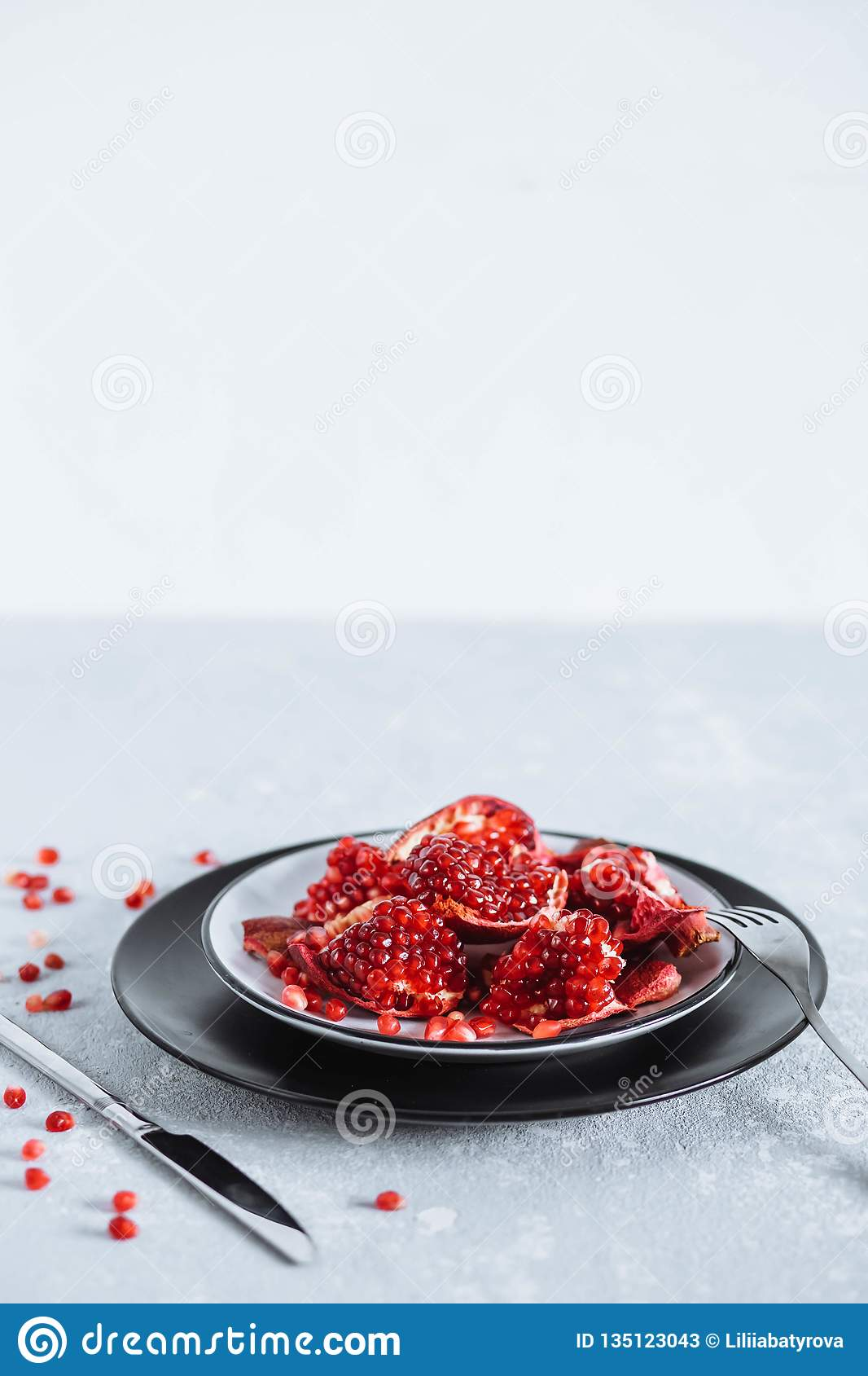 Beautiful slices of juicy red pomegranate on a gray table with Cutlery. Healthy food, fruit, diet