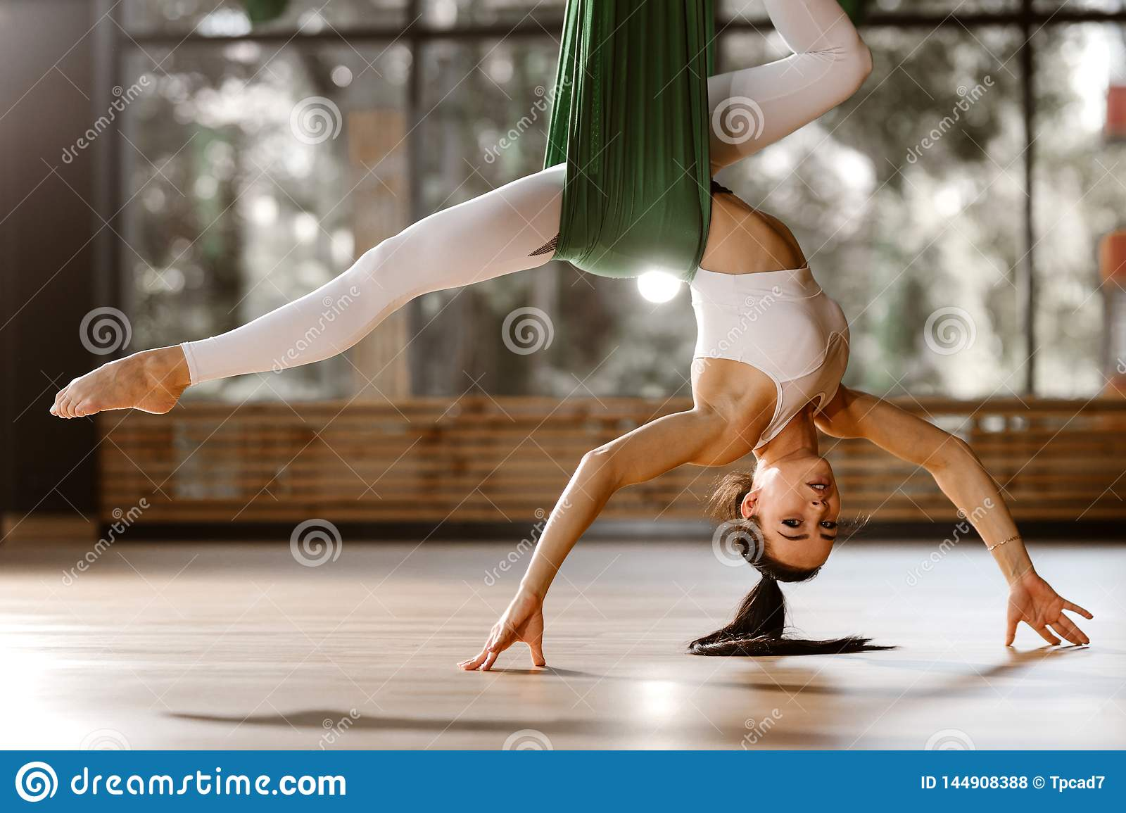 Beautiful slim dark-haired girl dressed in white sports top  and tights is doing stretching exercise on green hammock