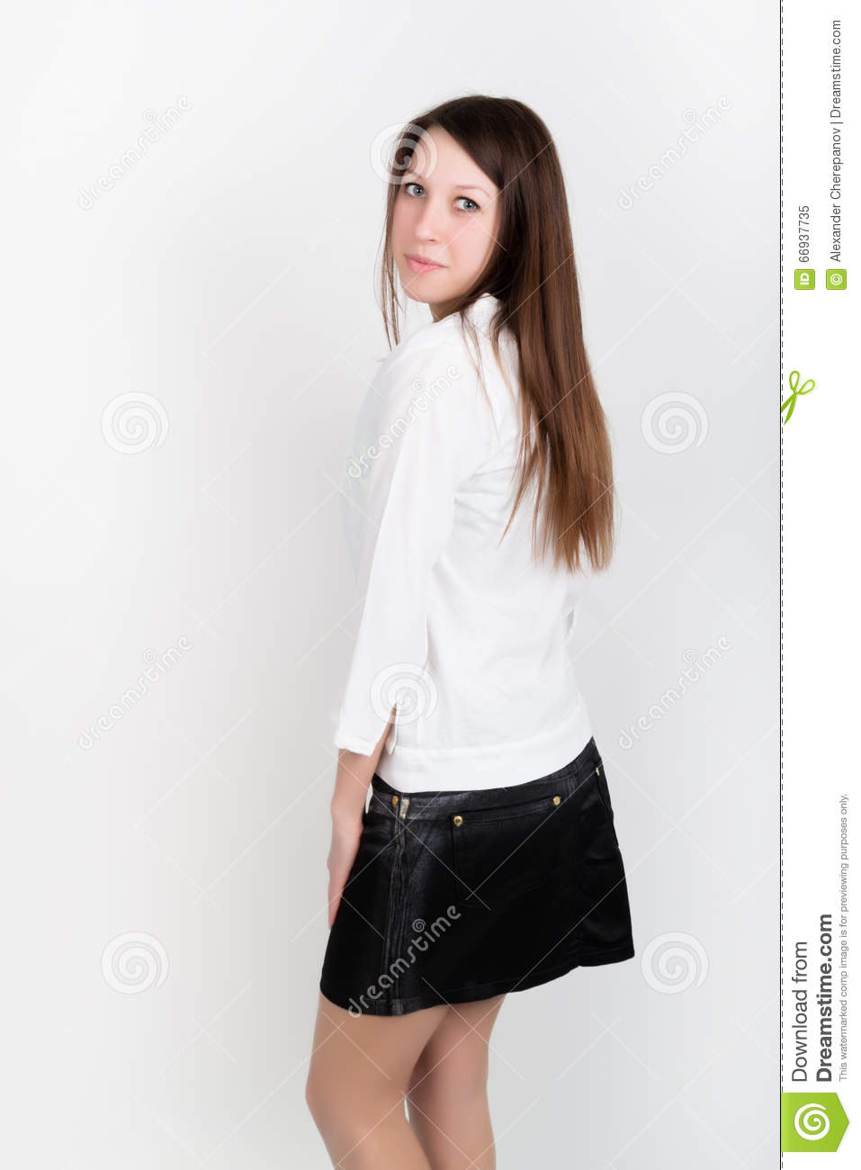 Beautiful Slim Girl In A Short Black Skirt And White Blouse Posing