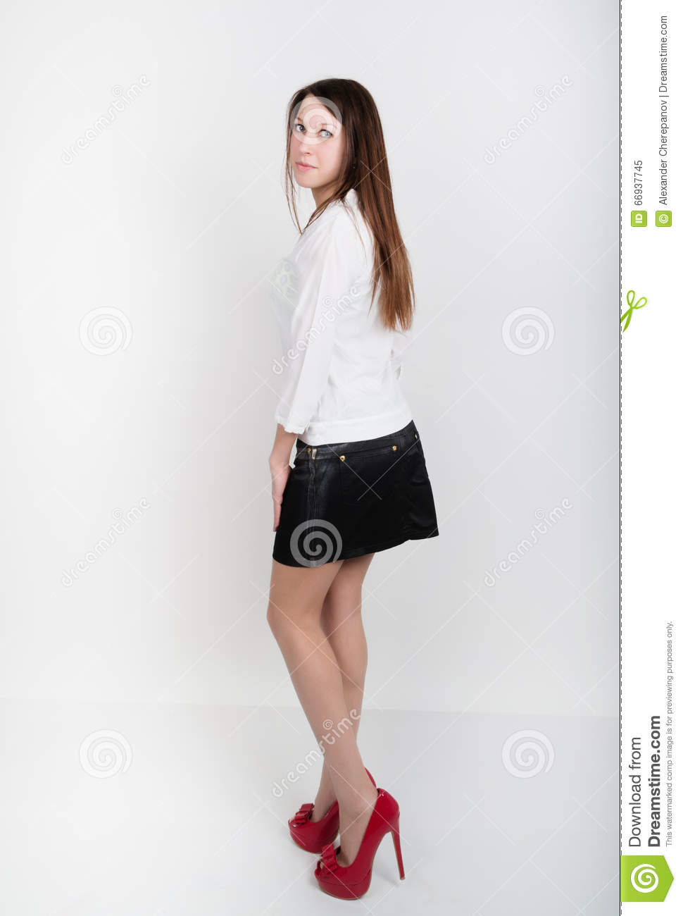 83e78302ef Beautiful slim girl in a short black skirt, white blouse and red shoes with  high heels, posing.