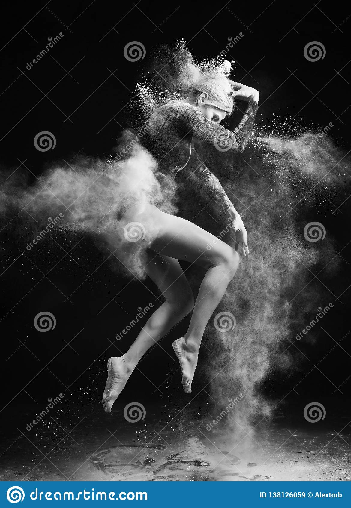 Beautiful slim girl wearing a gymnastic bodysuit covered with clouds of the flying white powder jumps dancing on a dark. Artistic