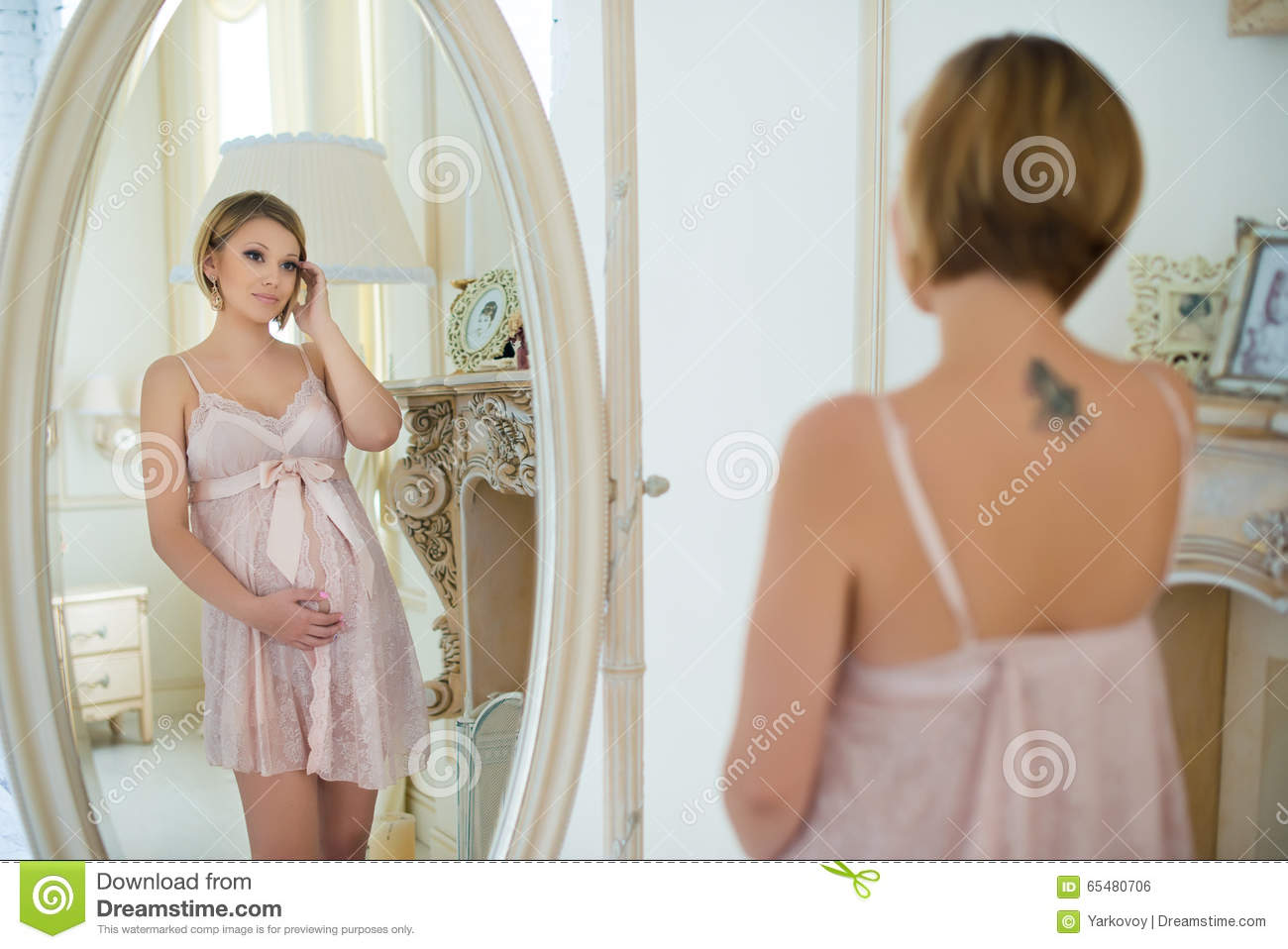 Beautiful Slim Pregnant Girl With A Tattoo On Shoulder Blade Looking
