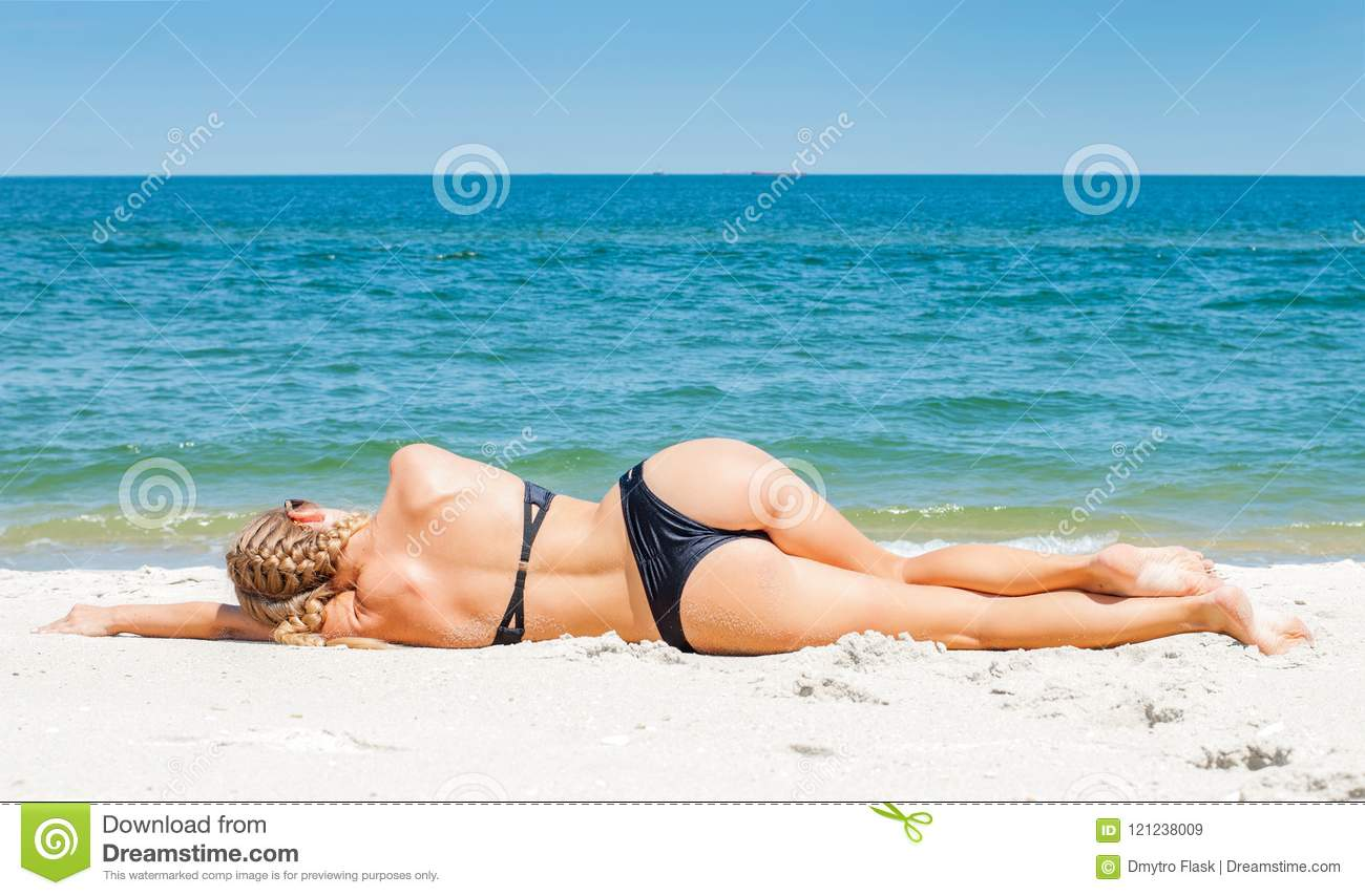 6d39185b86 Beautiful slim woman in bikini lying on sand and tanning on the beach