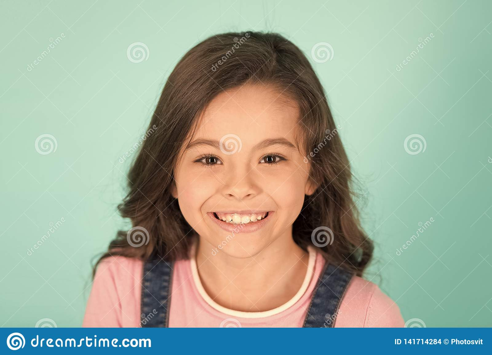 Beautiful smile. Child happy cheerful enjoy childhood. Girl curly hairstyle adorable smiling happy face. Kid charming