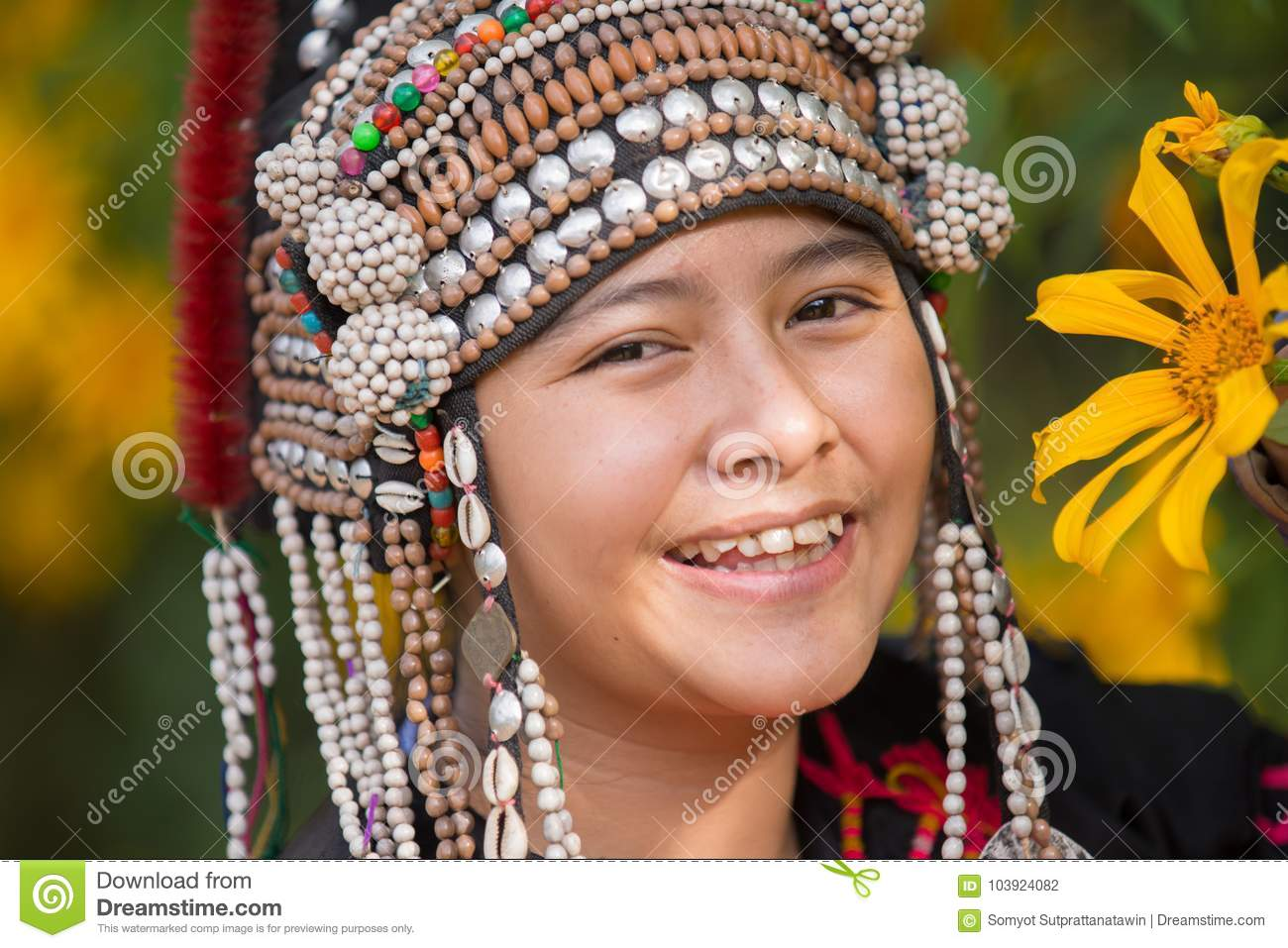 Beautiful smile young hill tribe girl in sunflowers garden.