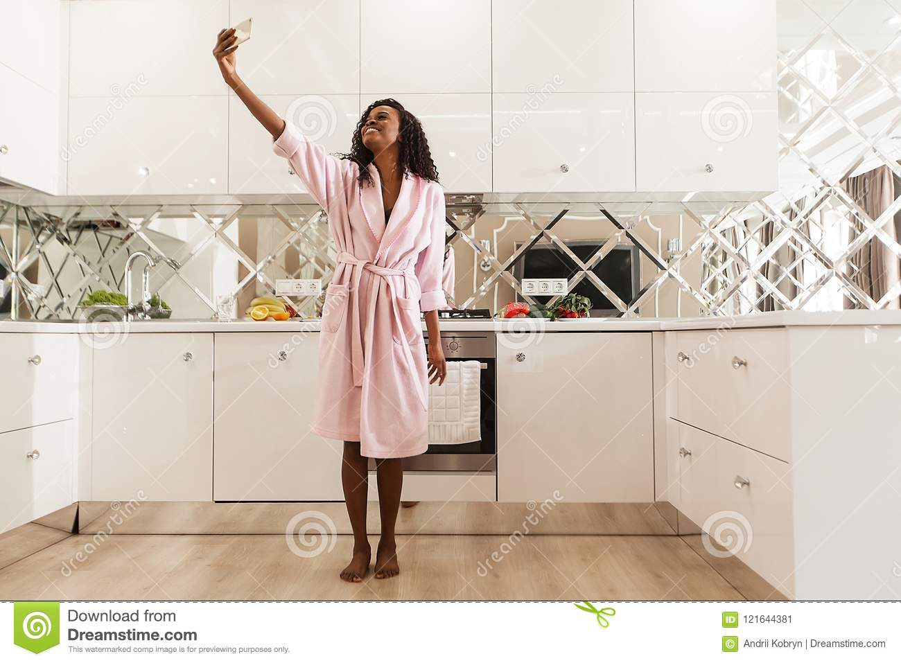 Beautiful smiling african woman with curly hair in pink bathrobe is taking selfie on the mobile phone. Modern kitchen