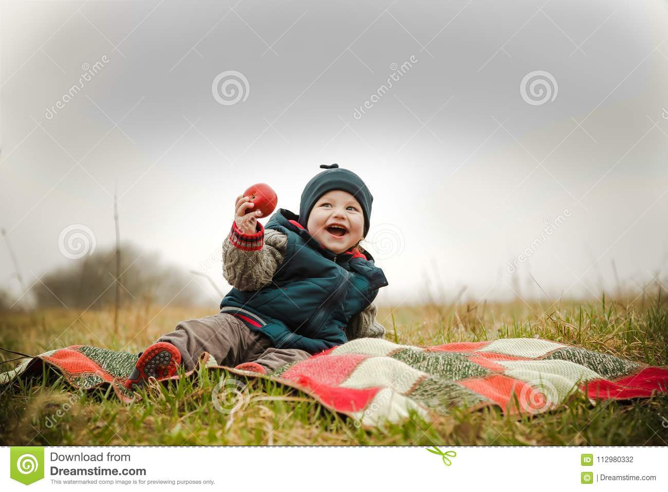 The child laughs at a picnic and eats a delicious apple