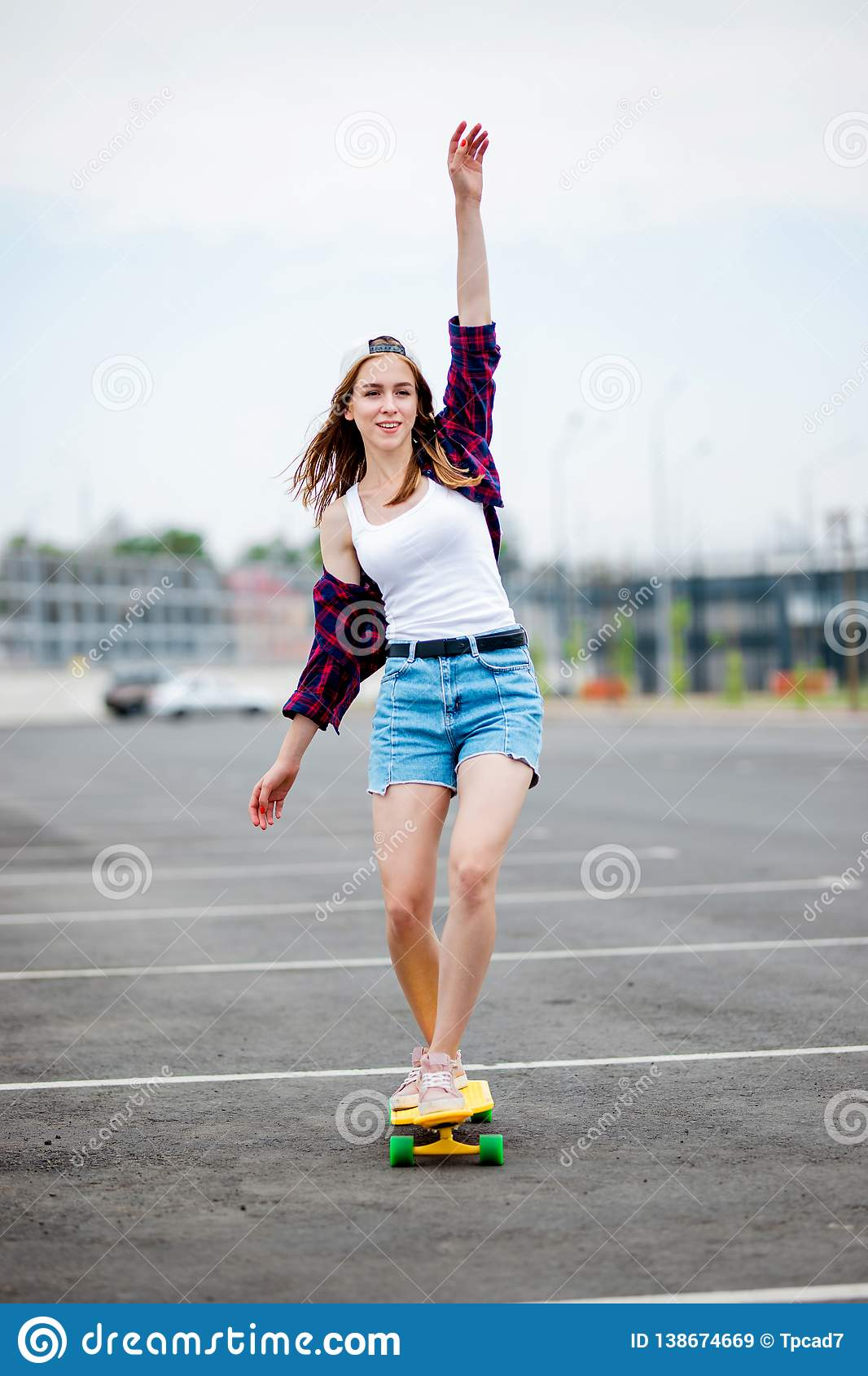 A beautiful smiling blond girl wearing checkered shirt, white cap and denim shorts is balancing on the yellow longboard