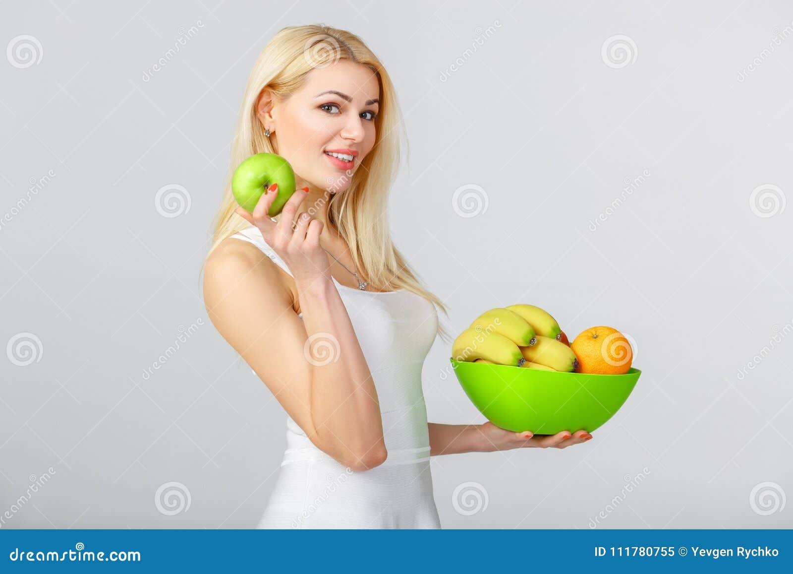 Woman in white dress showing fresh apple.