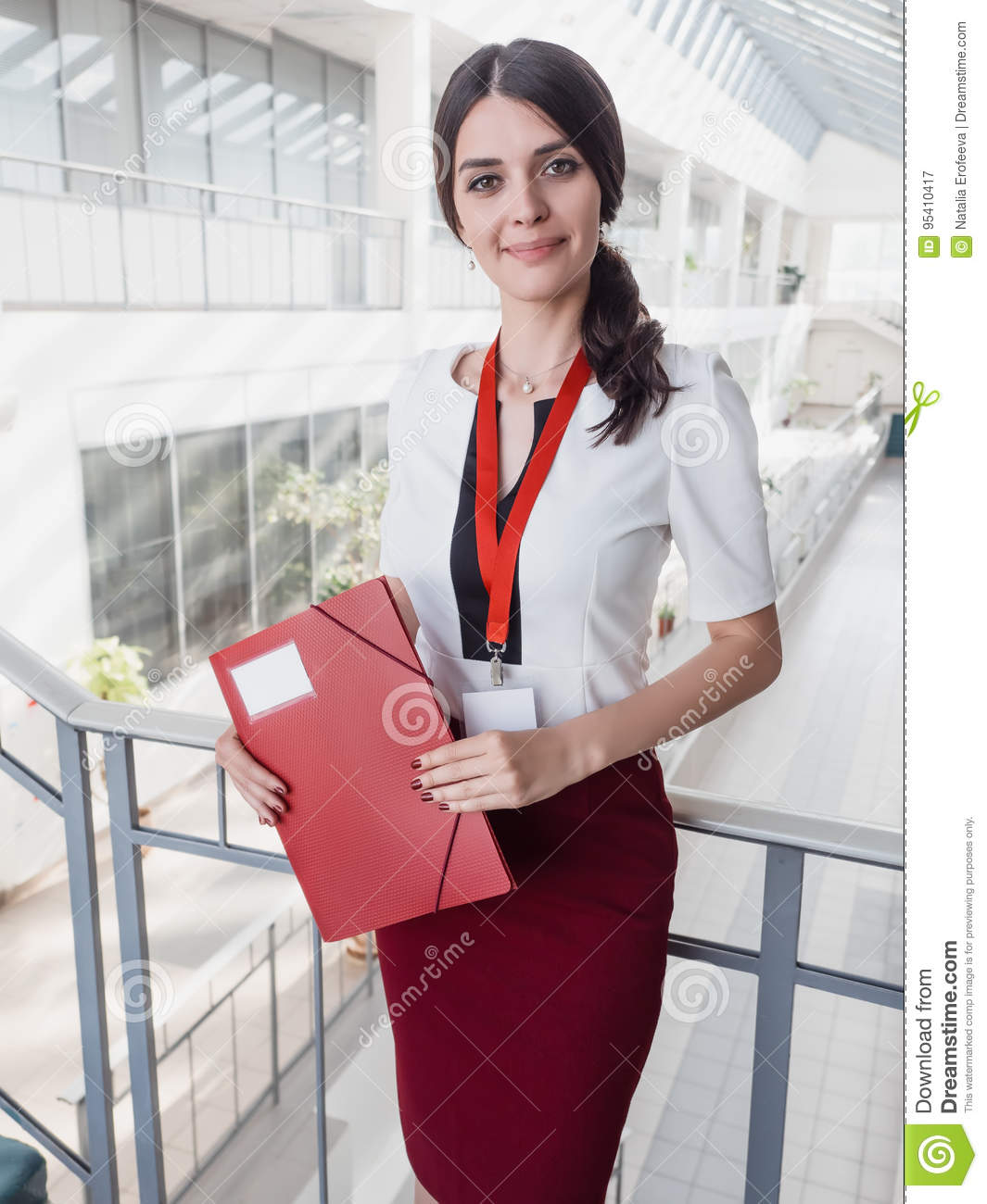 Beautiful Smiling Businesswoman Standing Against White Offices Background. Portrait of Business Woman With a Folder in Her Hands