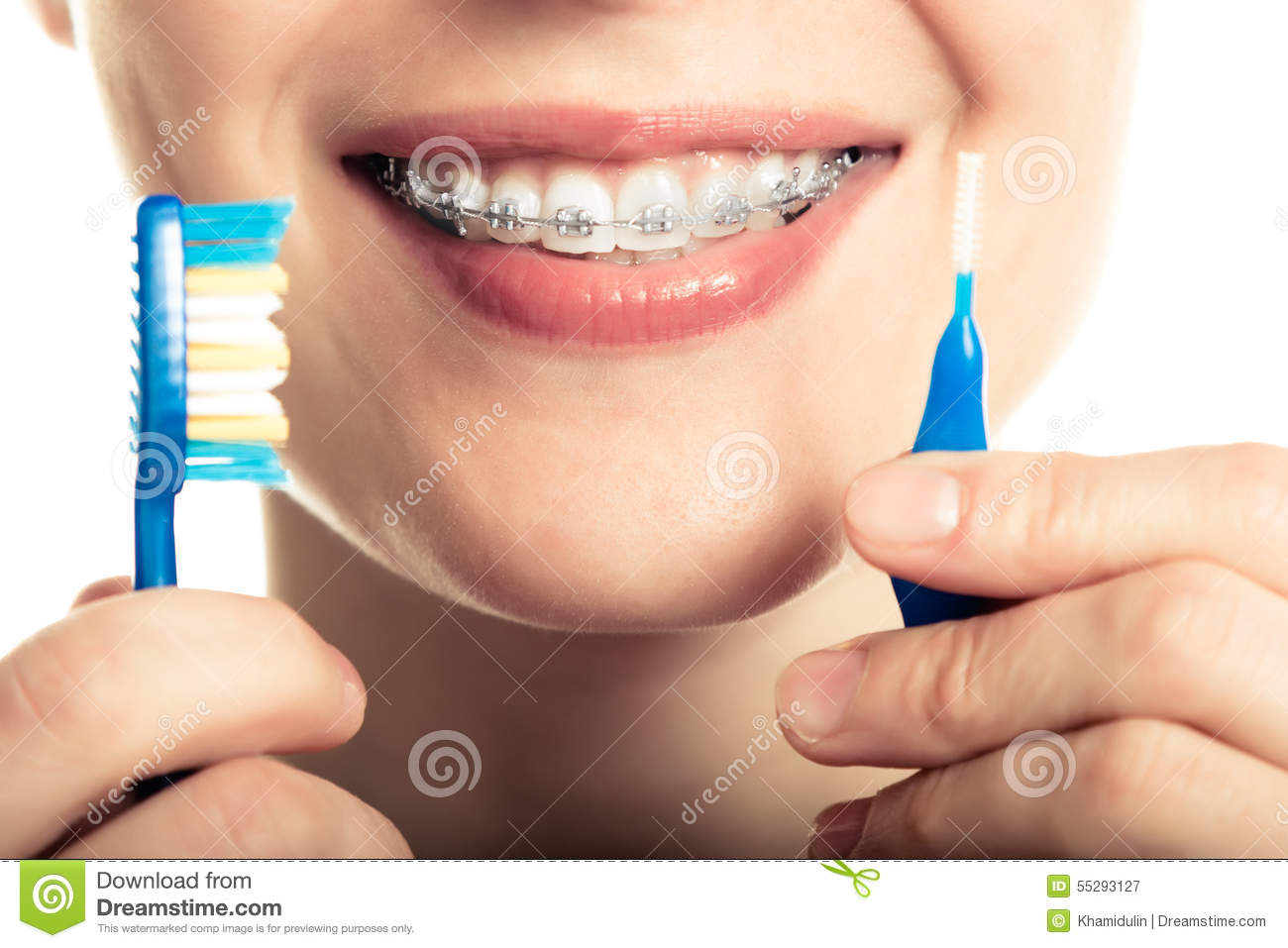 Beautiful smiling girl with retainer for teeth brushing teeth