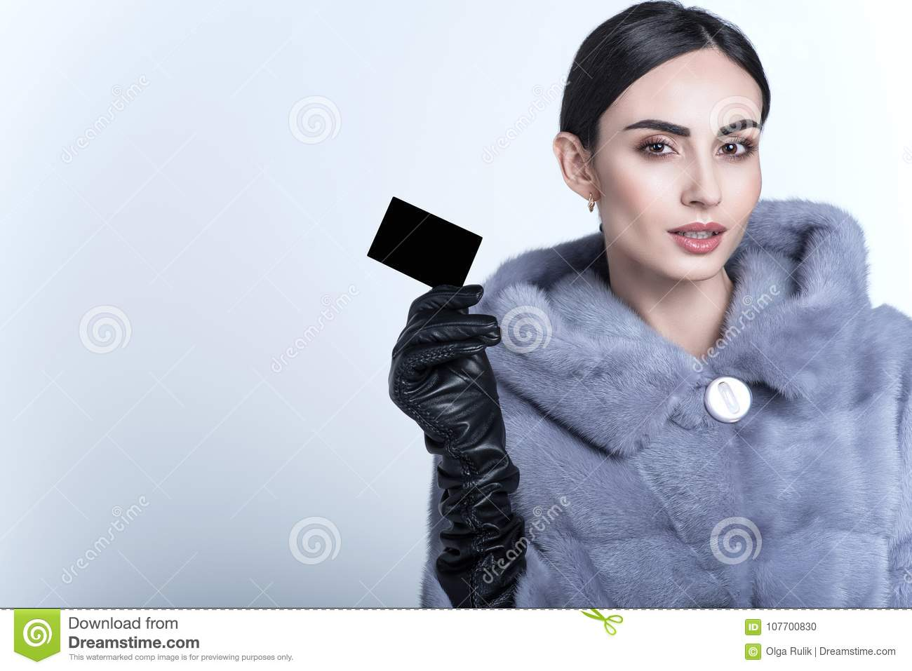 Beautiful smiling model wearing blue mink fur coat and long leather gloves holding black blank business card