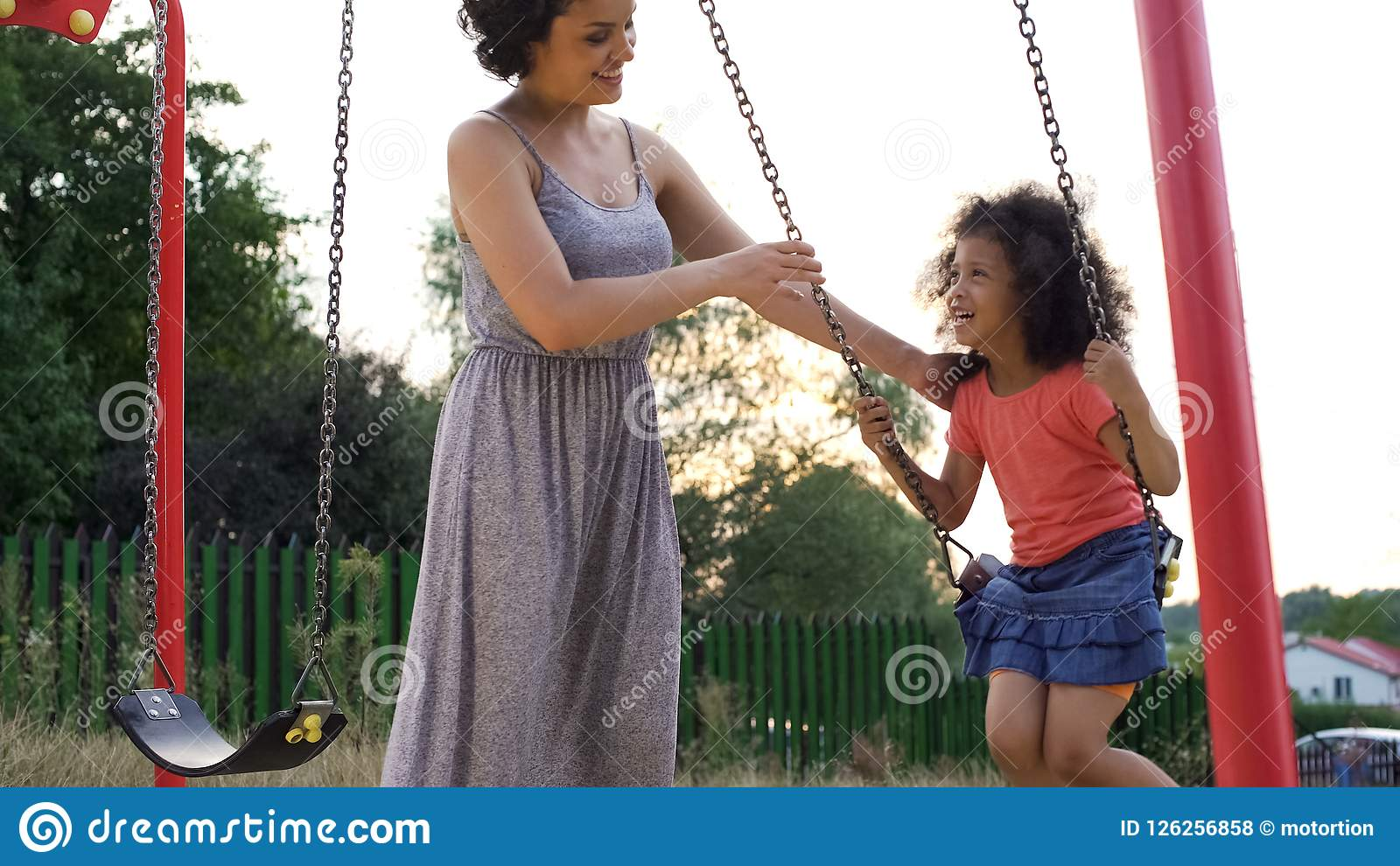 Beautiful smiling mother in grey dress swinging her favorite giggling daughter