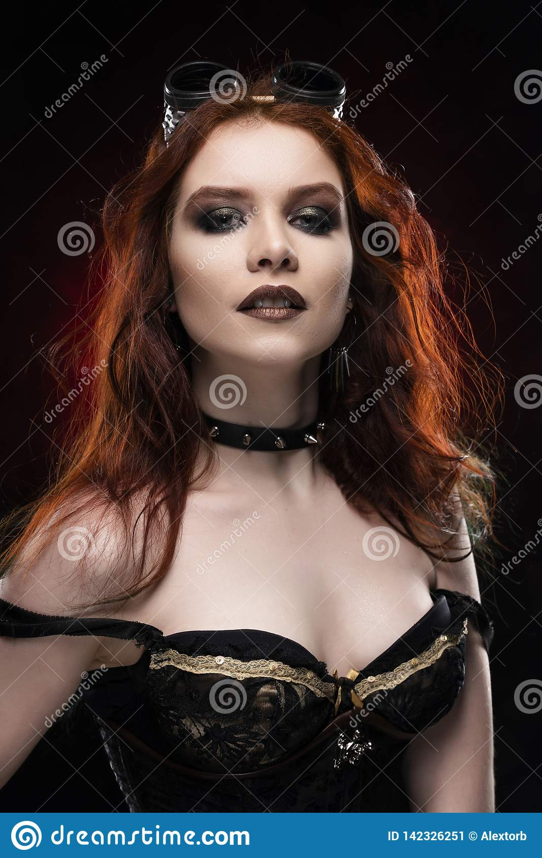 Beautiful smiling redhead cosplayer girl wearing a Victorian-style steampunk costume with a big breast in a deep neckline on red