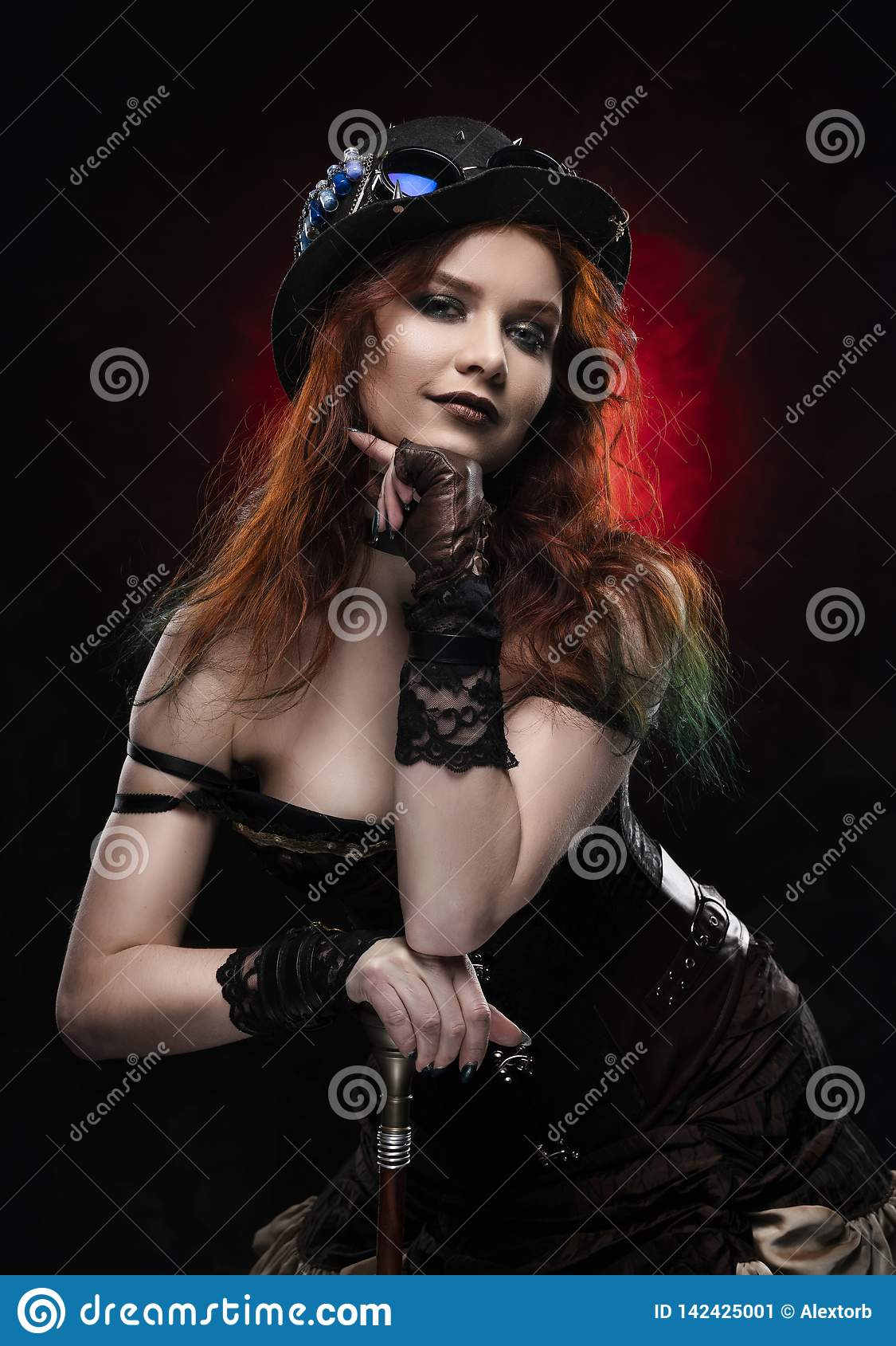 Beautiful smiling redhead cosplayer girl wearing a Victorian-style steampunk costume and hat with a big breast in a deep neckline
