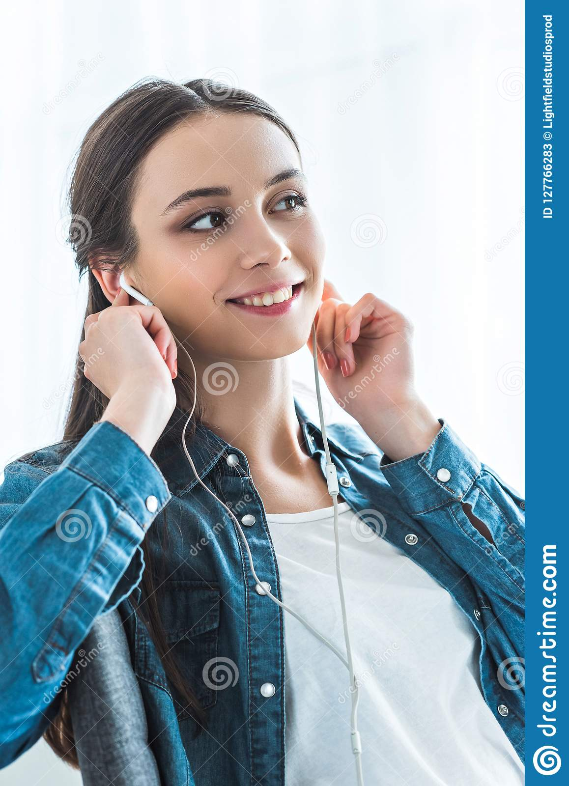 beautiful smiling teenage girl listening music in earphones