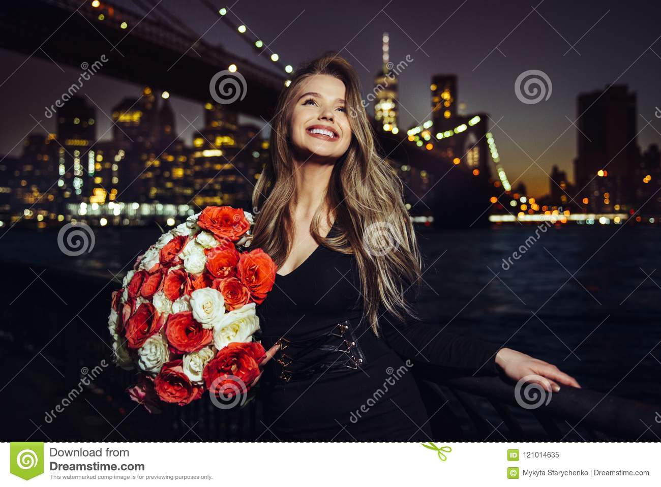 Beautiful smiling woman enjoy her birthday rose flower bouquet present at the party in the city.