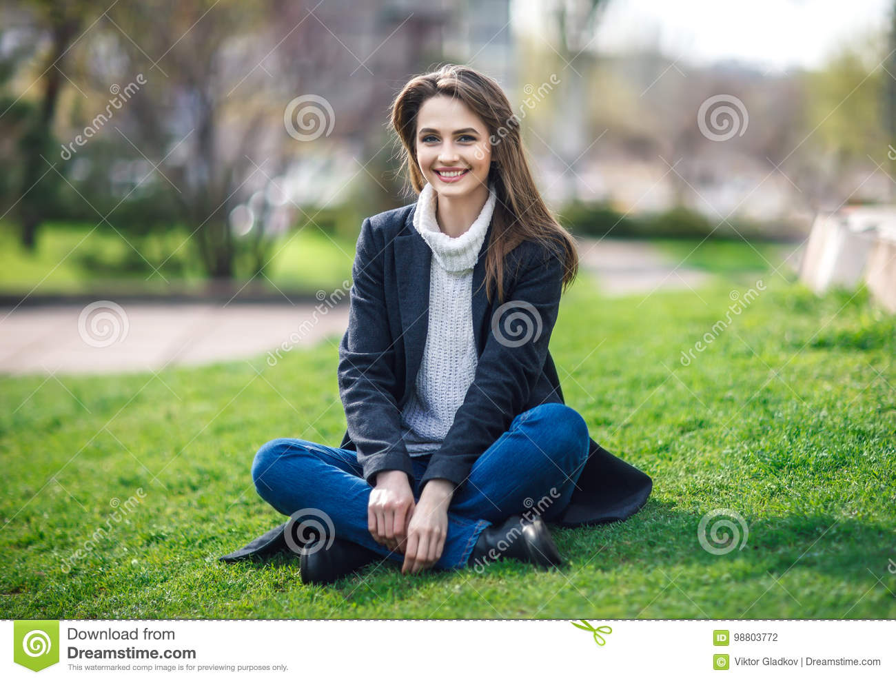 Beautiful smiling woman sitting on a grass outdoor