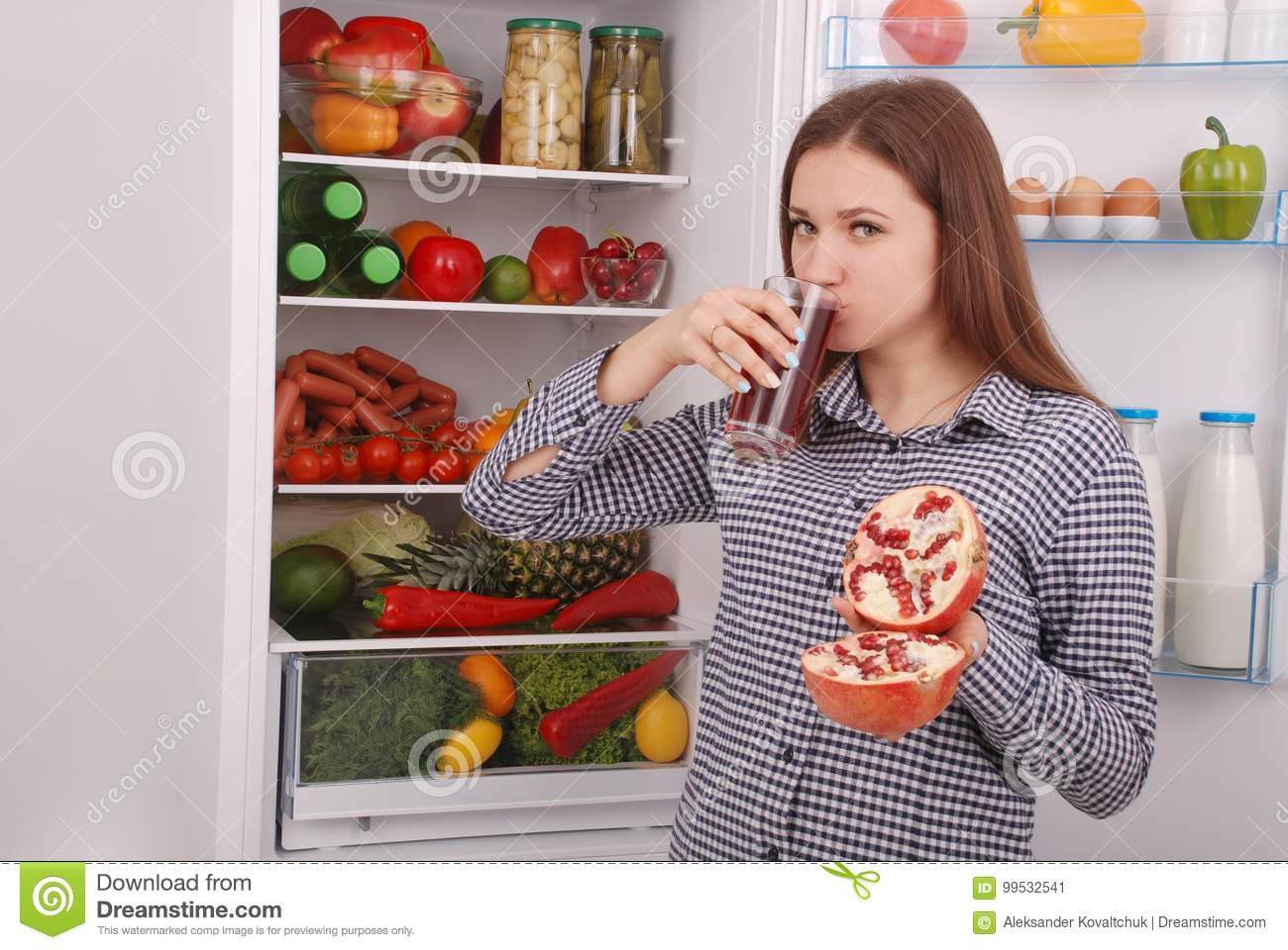 Beautiful smiling young girl holds a glass of pomegranate juice and garnet