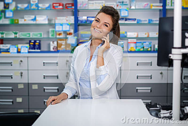 Beautiful smiling young woman pharmacist talking on the cell phone in pharmacy.