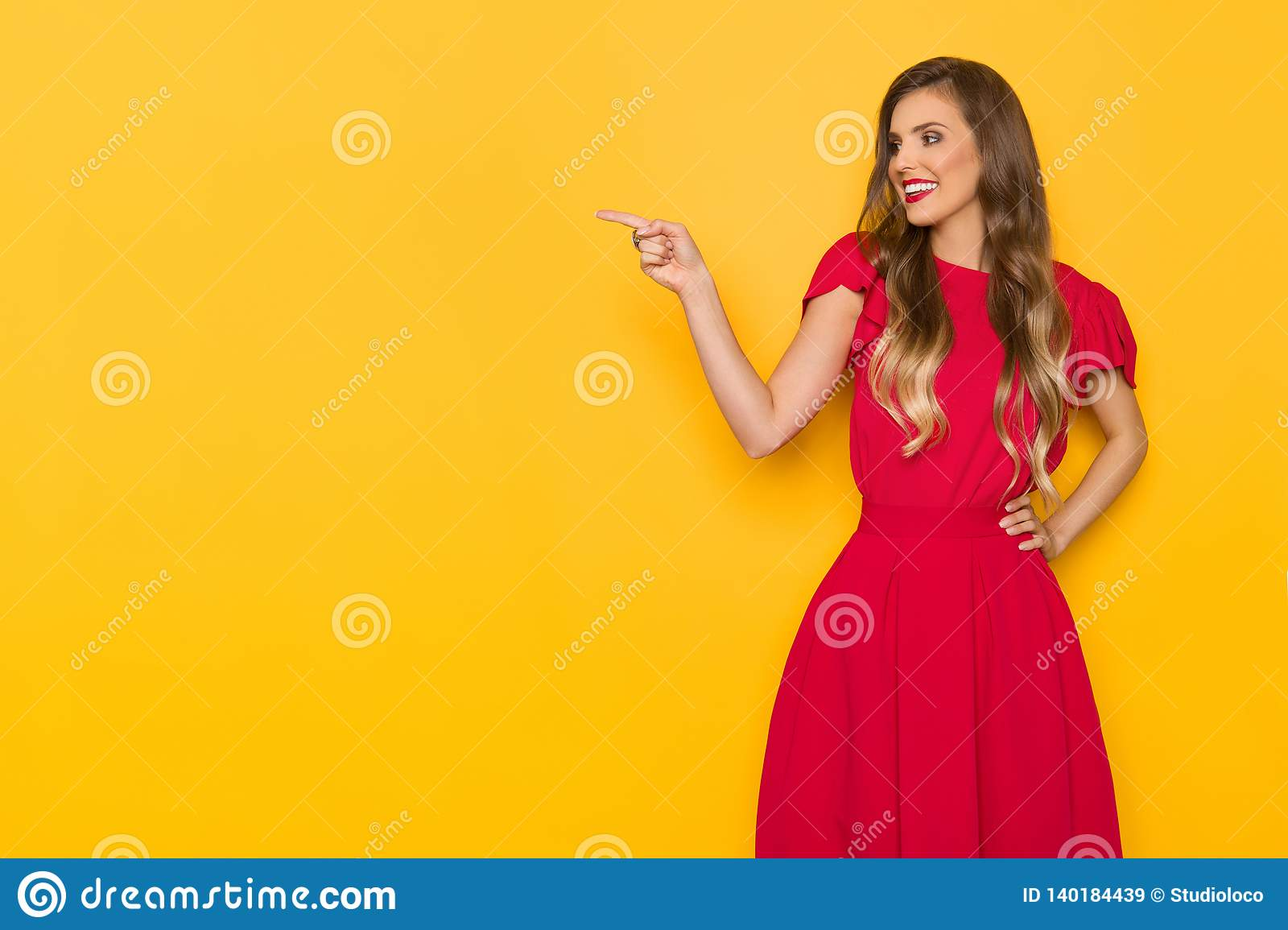 Beautiful Smiling Young Woman In Red Dress Is Pointing And Looking Away