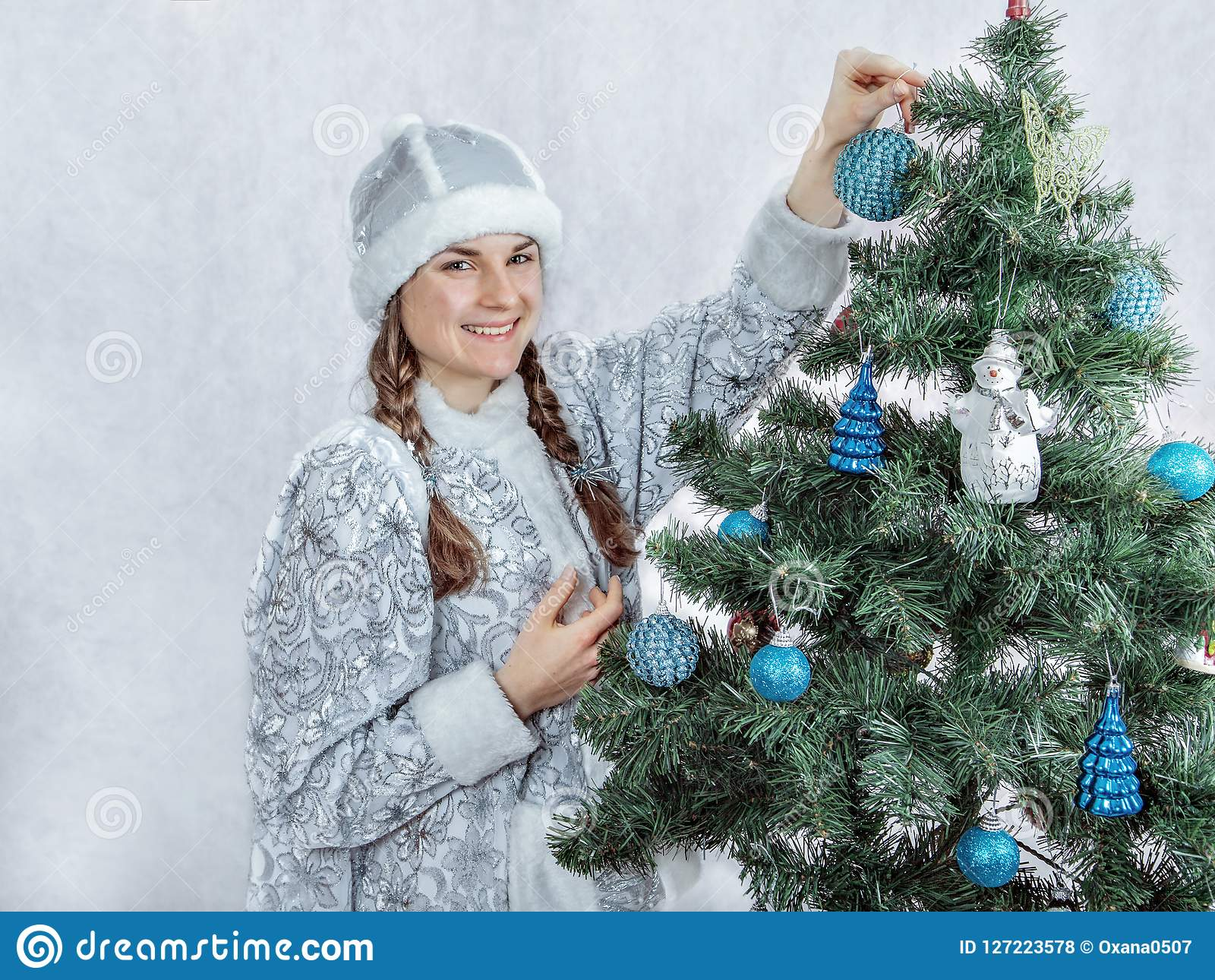 Beautiful snow girl is decorating a Christmas tree. New Year and Christmas.
