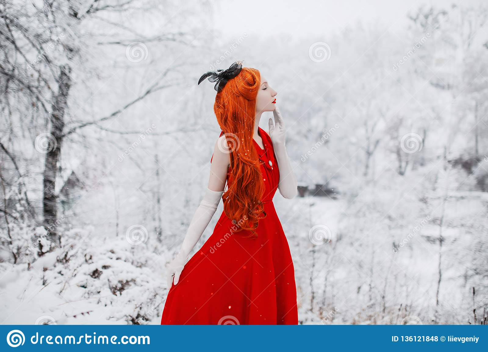 Beautiful snow maiden girl with red hair on winter nature. Beautiful redhead retro woman in red dress and with long gloves on back
