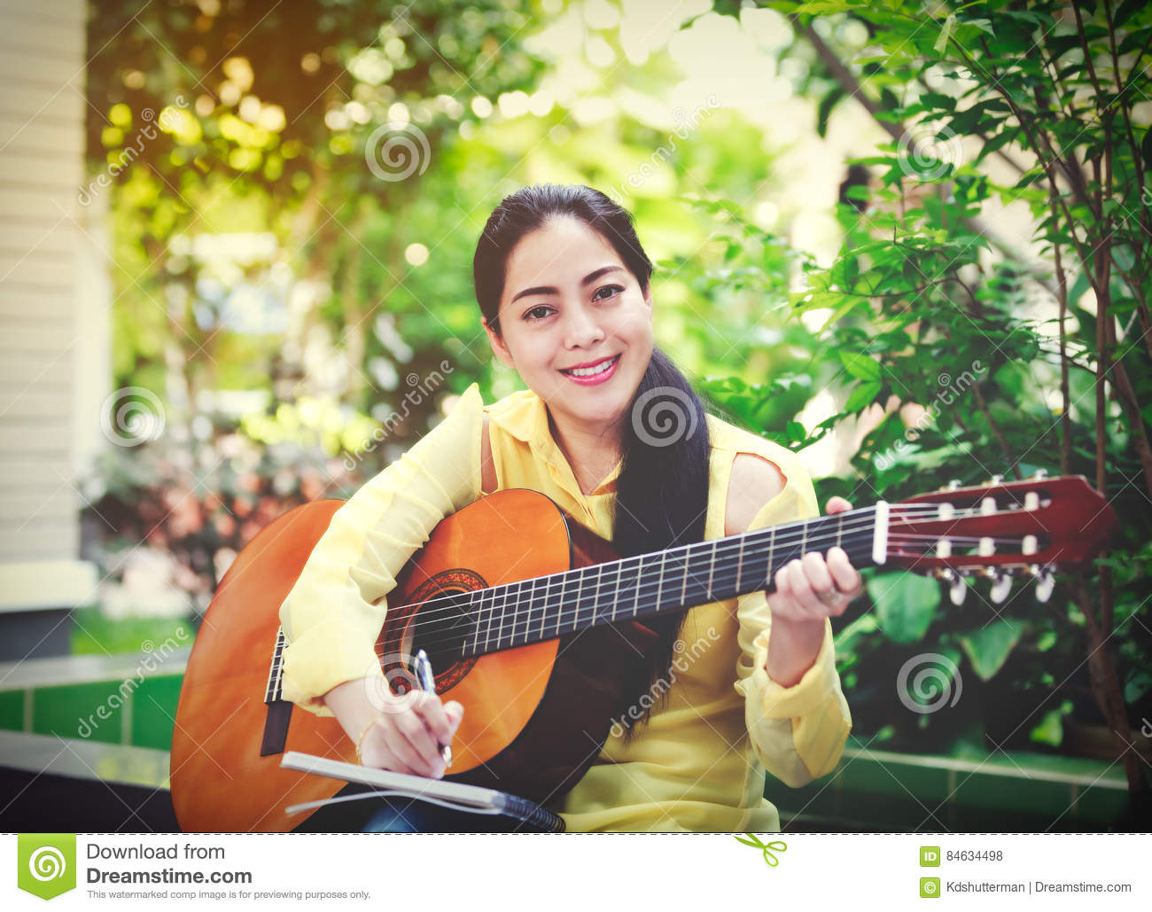 Beautiful songwriter writing on note paper with acoustic guitar
