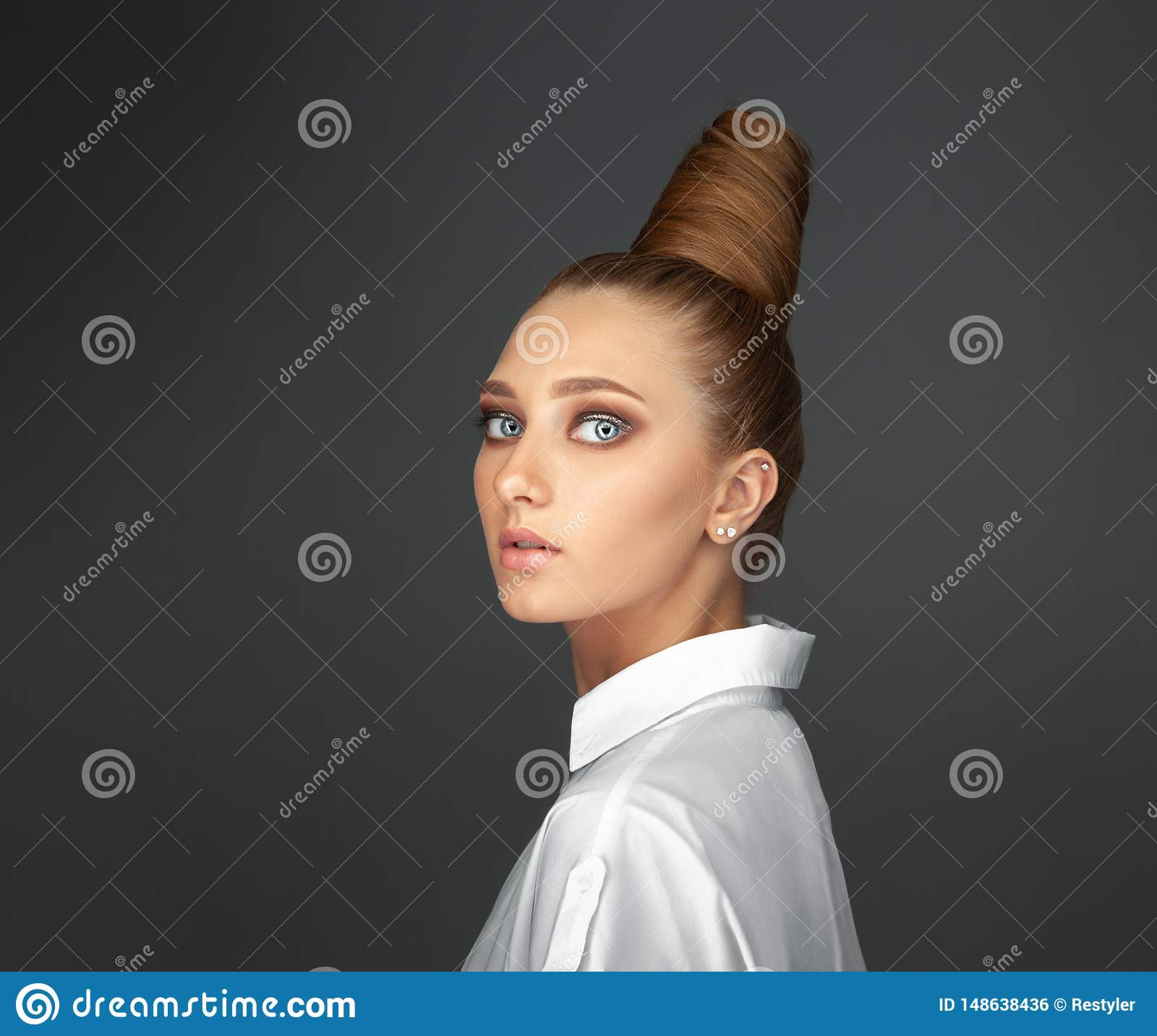 Beautiful spectacular blonde lady with an unusual high hairdo with big blue eyes on a dark background