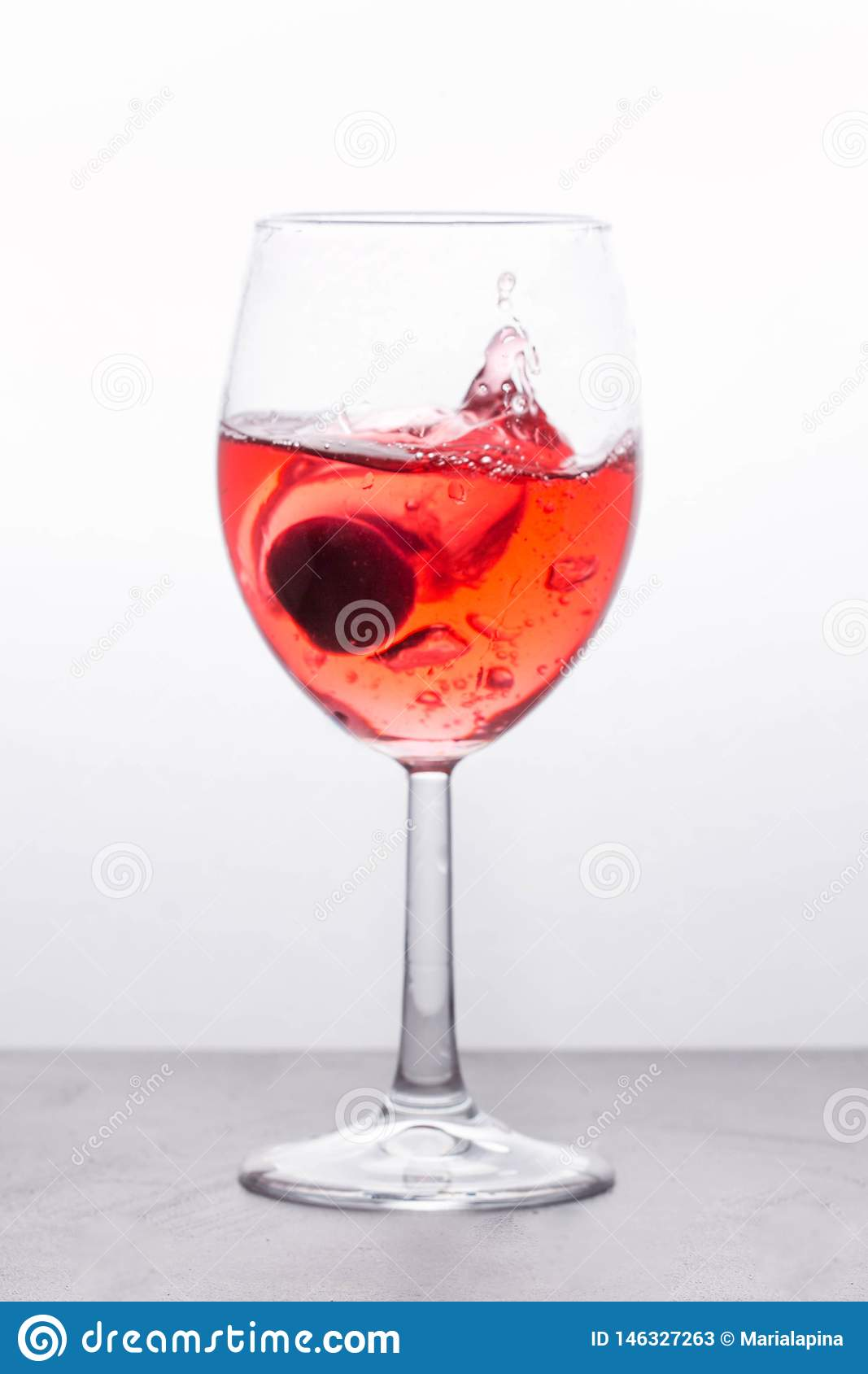 Beautiful splash in wine glass with a pink drink and cherry berrie. Light background