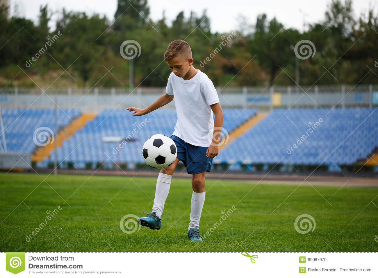 a cute teenage boy hitting the football ball on a stadium background