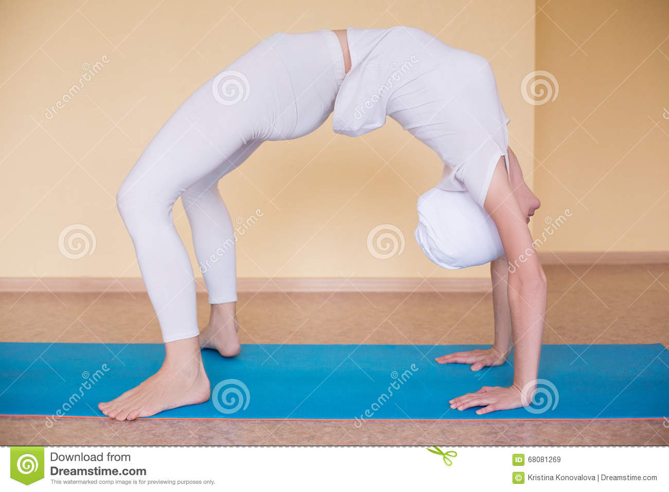 Beautiful sporty fit yogini woman practices yoga asana chakrasana (or urdva dhanurasana)